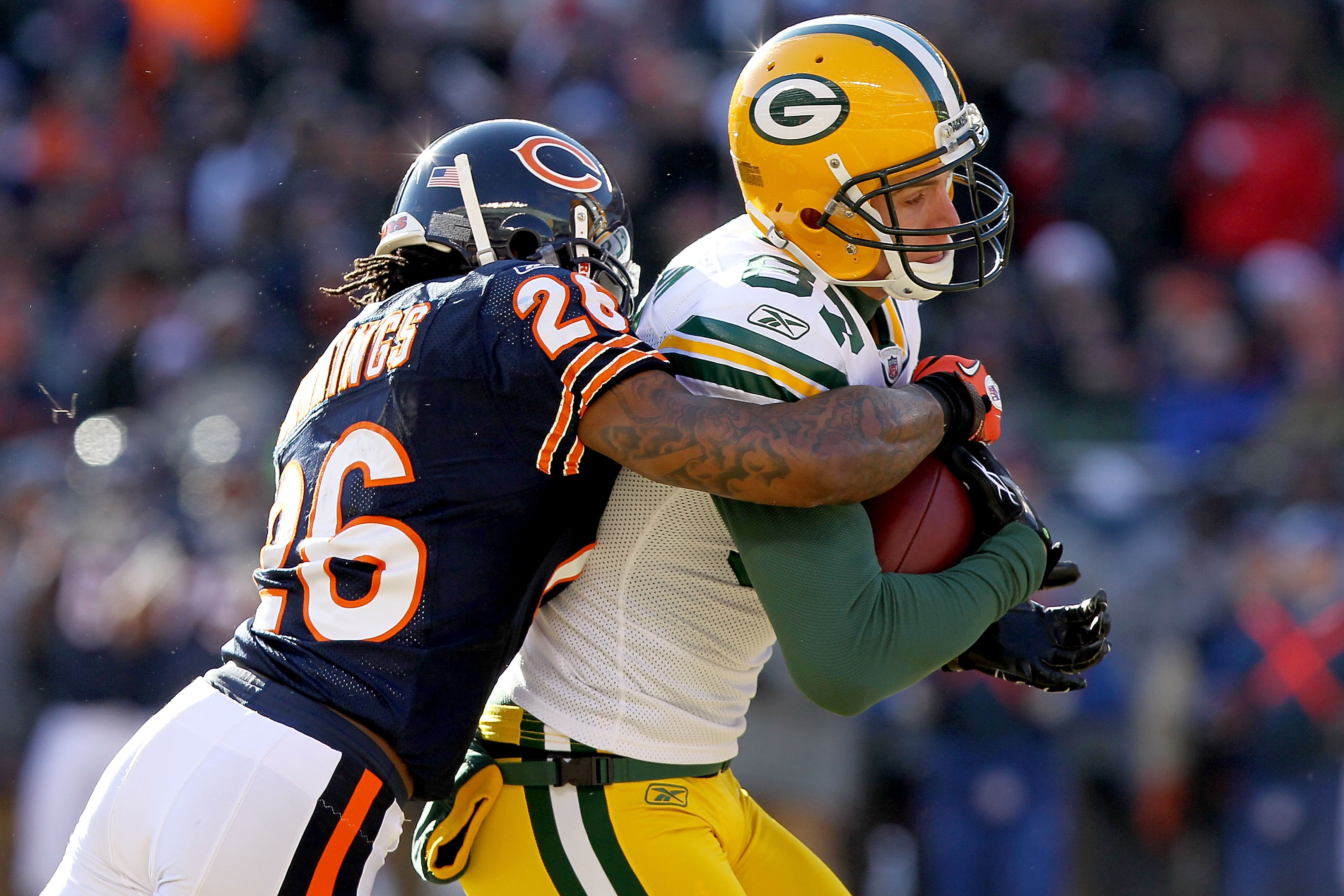 CHICAGO, IL - JANUARY 23:  Wide receiver Jordy Nelson #87 of the Green Bay Packers catches a 22-yard pass as he is tackled by Tim Jennings #26 of the Chicago Bears in the first quarter of the NFC Championship Game at Soldier Field on January 23, 2011 in C
