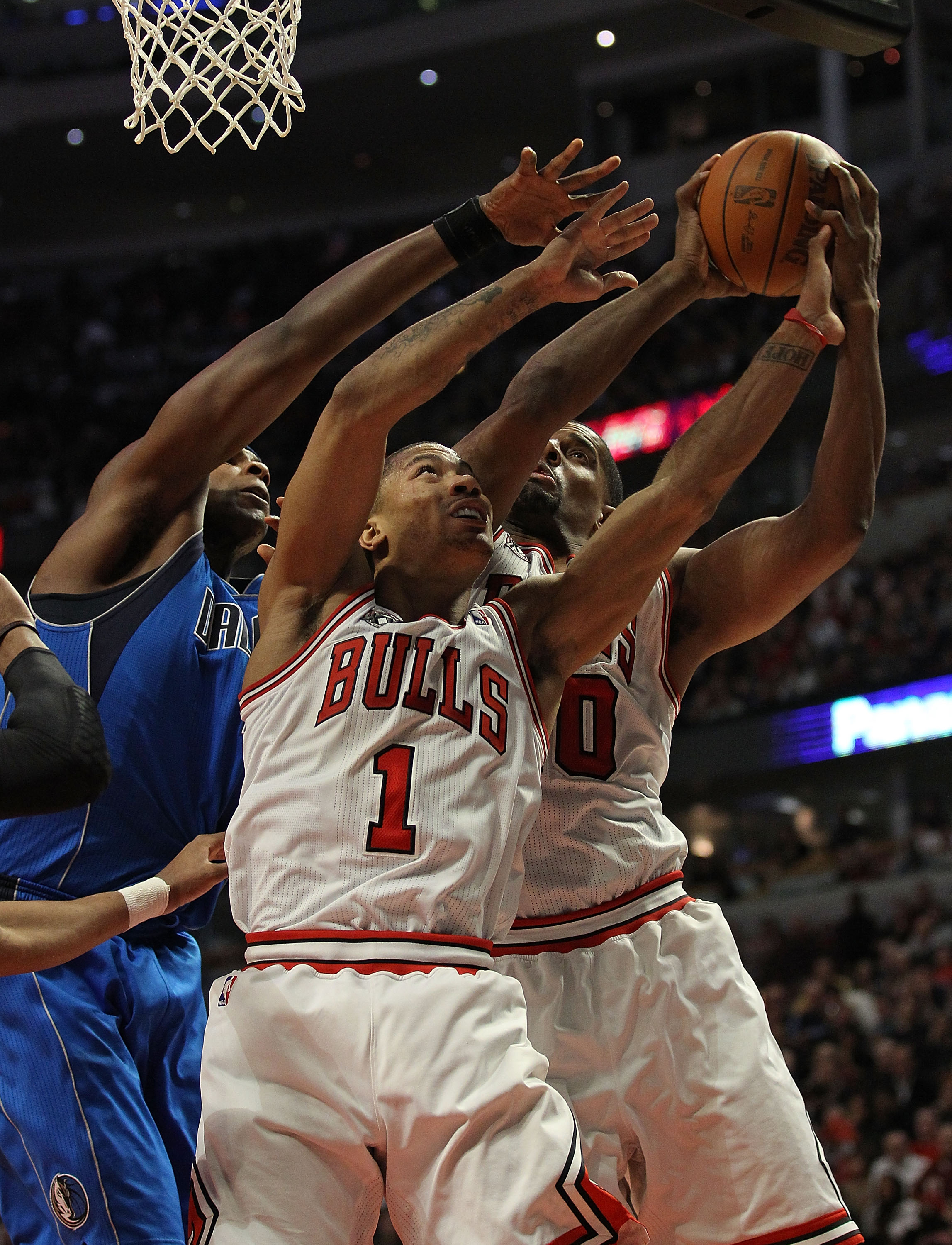 CHICAGO, IL - JANUARY 20: Derrick Rose #1 and Kurt Thomas #40 of the Chicago Bulls battle for a rebound with Brendan Haywood #33 of the Dallas Mavericks at the United Center on January 20, 2011 in Chicago, Illinois. The Bulls defeated the Mavericks 82-77.
