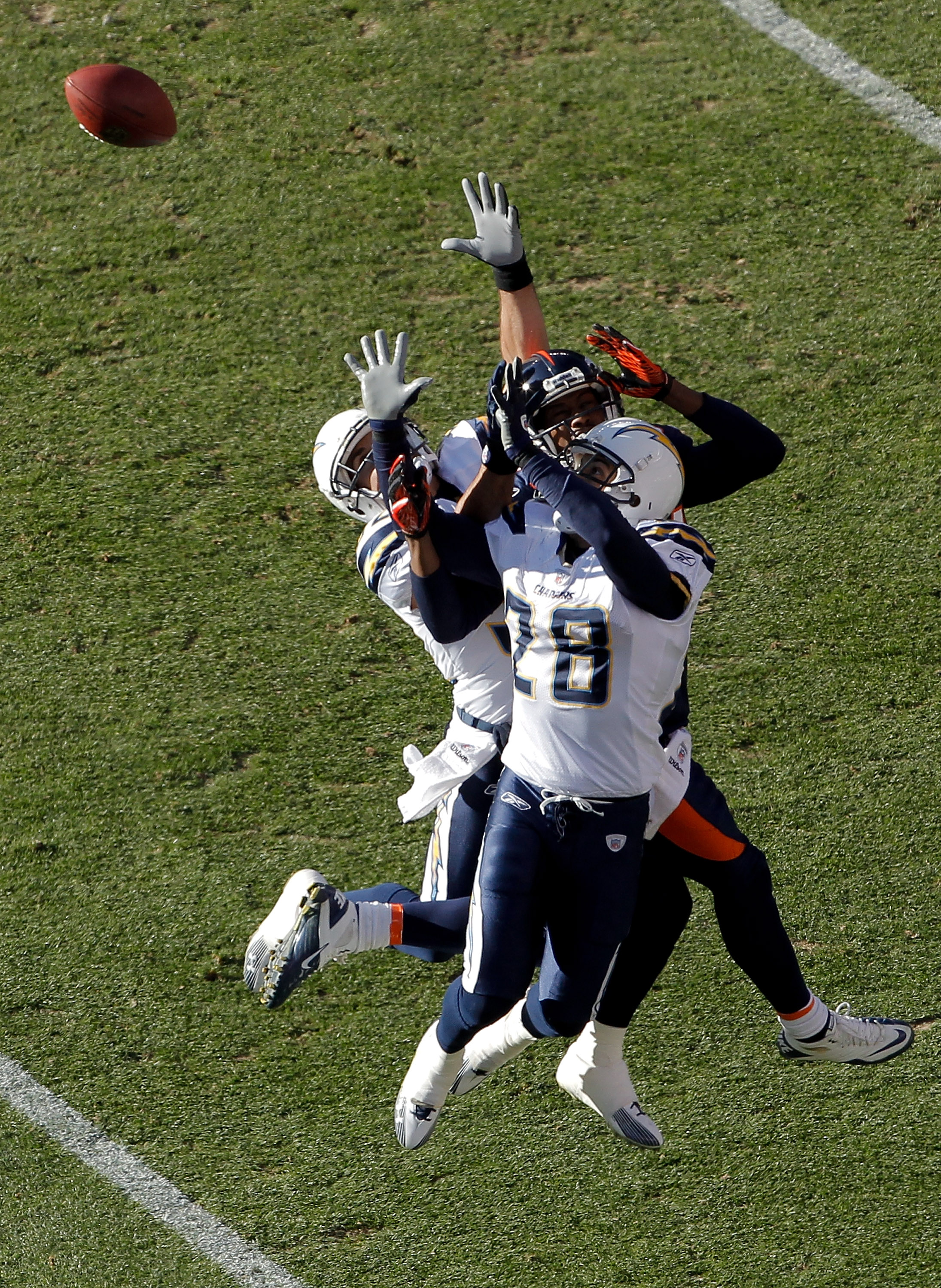 DENVER, CO - JANUARY 2:  Safety Eric Weddle #32 of the San Diego Chargers makes an interception on a pass intended for wide receiver Brandon Lloyd #84 of the Denver Broncos as they battle in the air with safety Steve Gregory #28 during the first quarter a