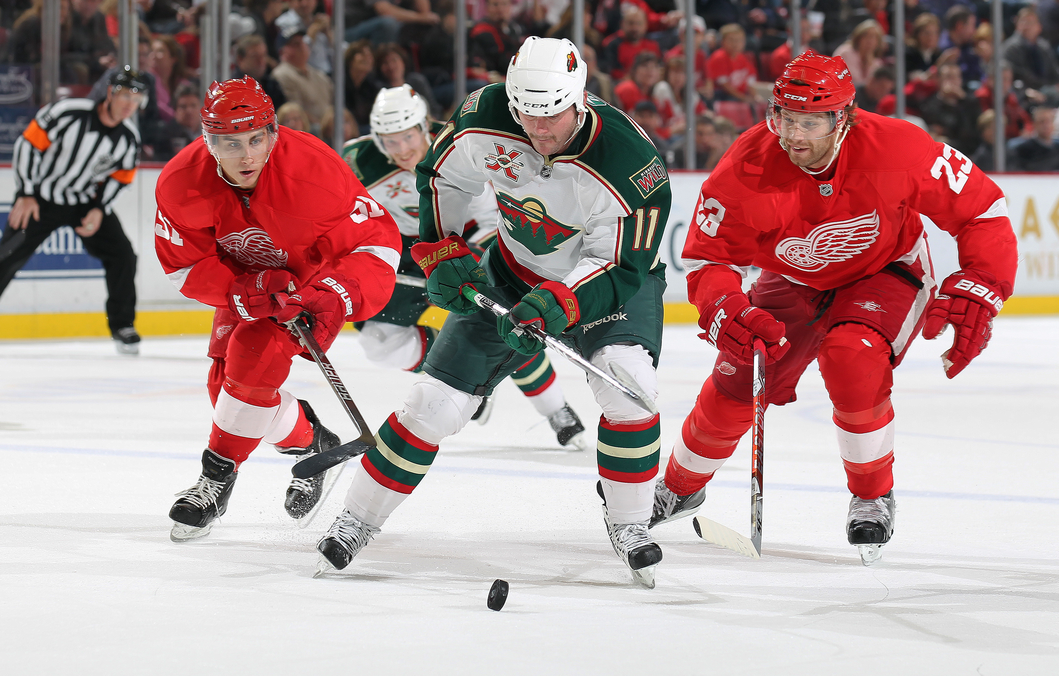 DETROIT, MI - NOVEMBER 19:  John Madden #11 of the Minnesota Wild skates in on a break while being checked by Valtteri Filppula #51 and Brad Stuart #23 of the Detroit Red Wings in a game on November 19, 2010 at the Joe Louis Arena in Detroit, Michigan. Th