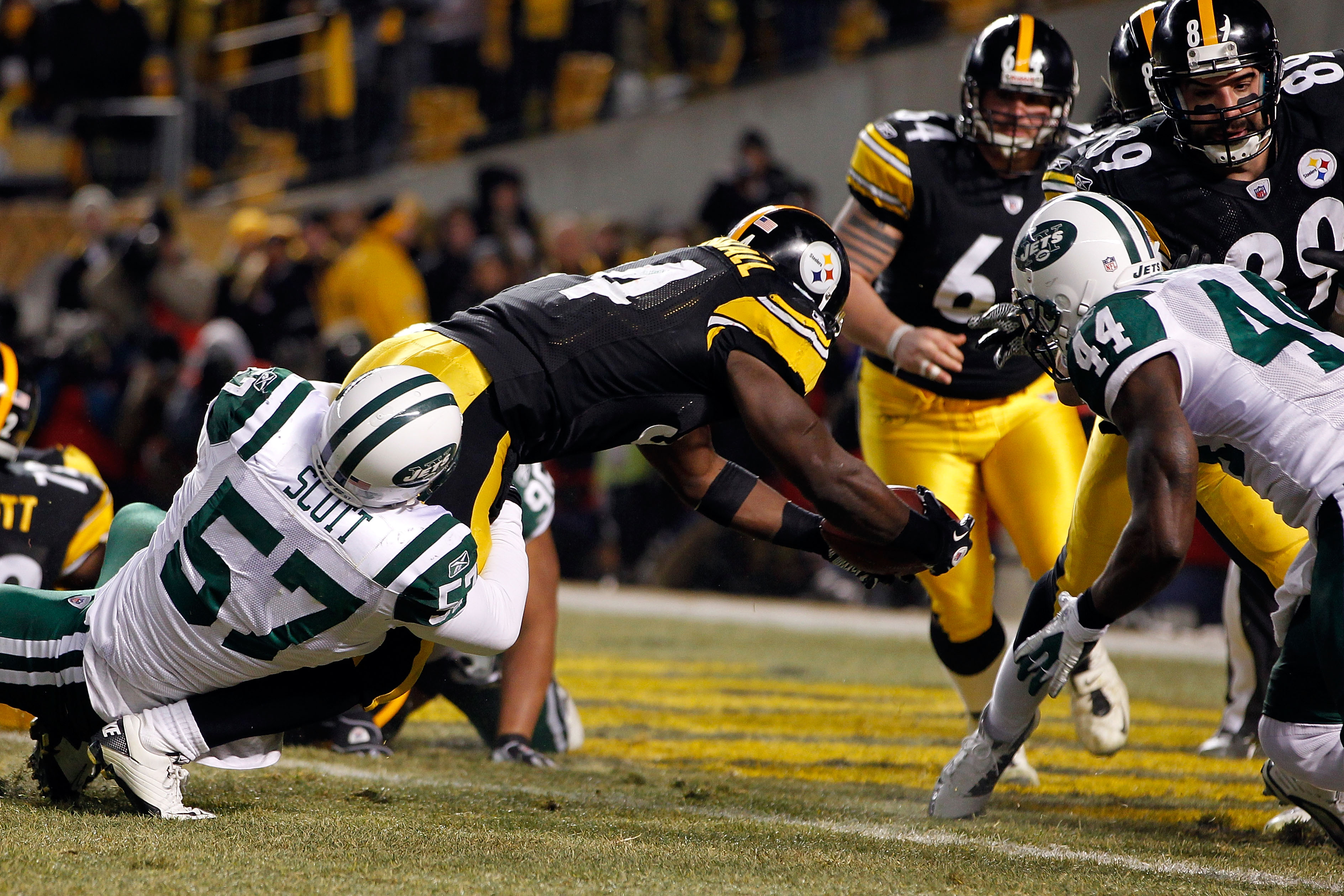 PITTSBURGH, PA - JANUARY 23:  Rashard Mendenhall #34 of the Pittsburgh Steelers scores a first quarter touchdown as Bart Scott #57 and James Ihedigbo #44 of the New York Jets attemps to tackle during the 2011 AFC Championship game at Heinz Field on Januar