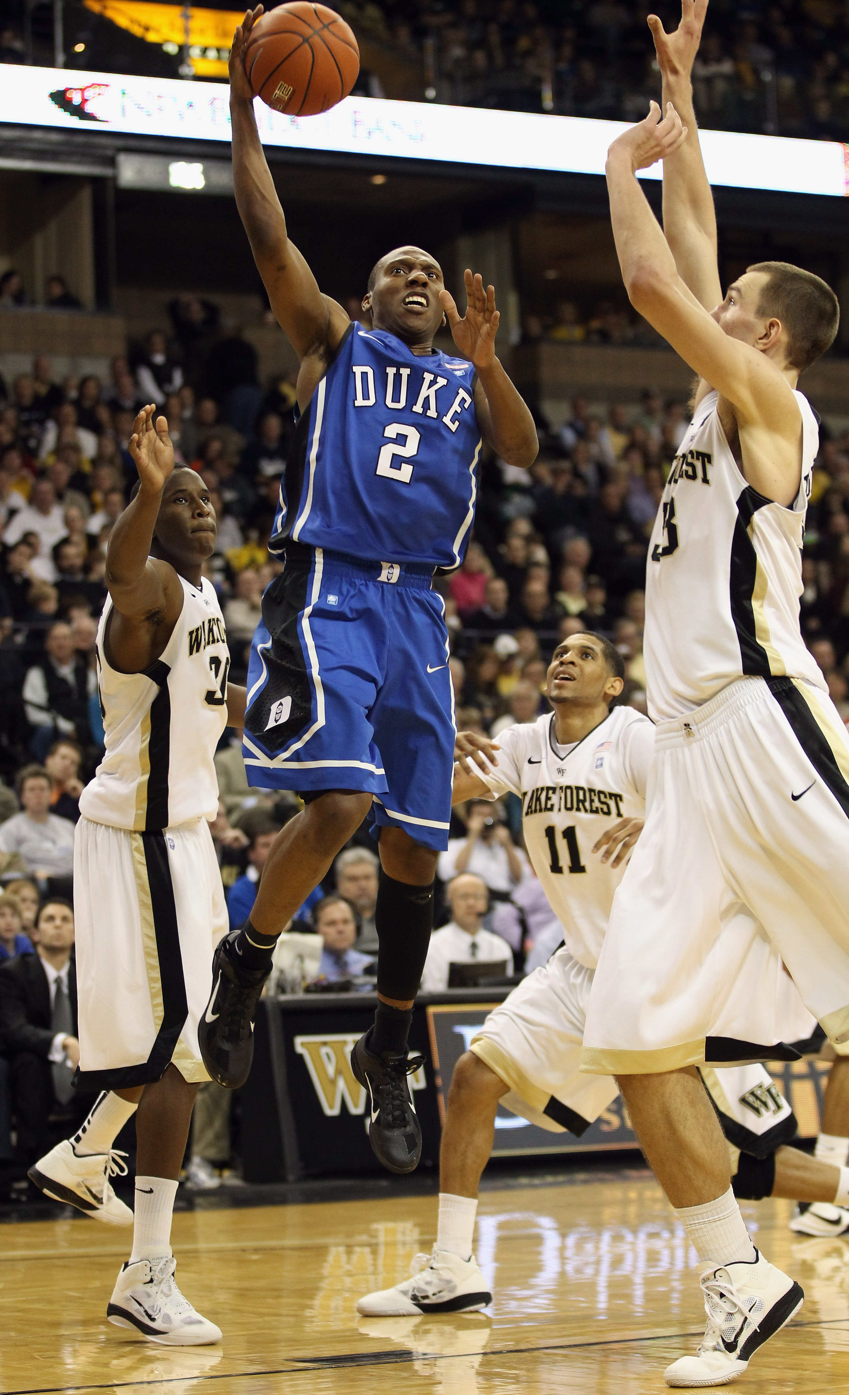 WINSTON SALEM, NC - JANUARY 22:  Nolan Smith #2 of the Duke Blue Devils drives to the basket on the defense of the Wake Forest Demon Deacons during their game at Lawrence Joel Coliseum on January 22, 2011 in Winston Salem, North Carolina.  (Photo by Stree
