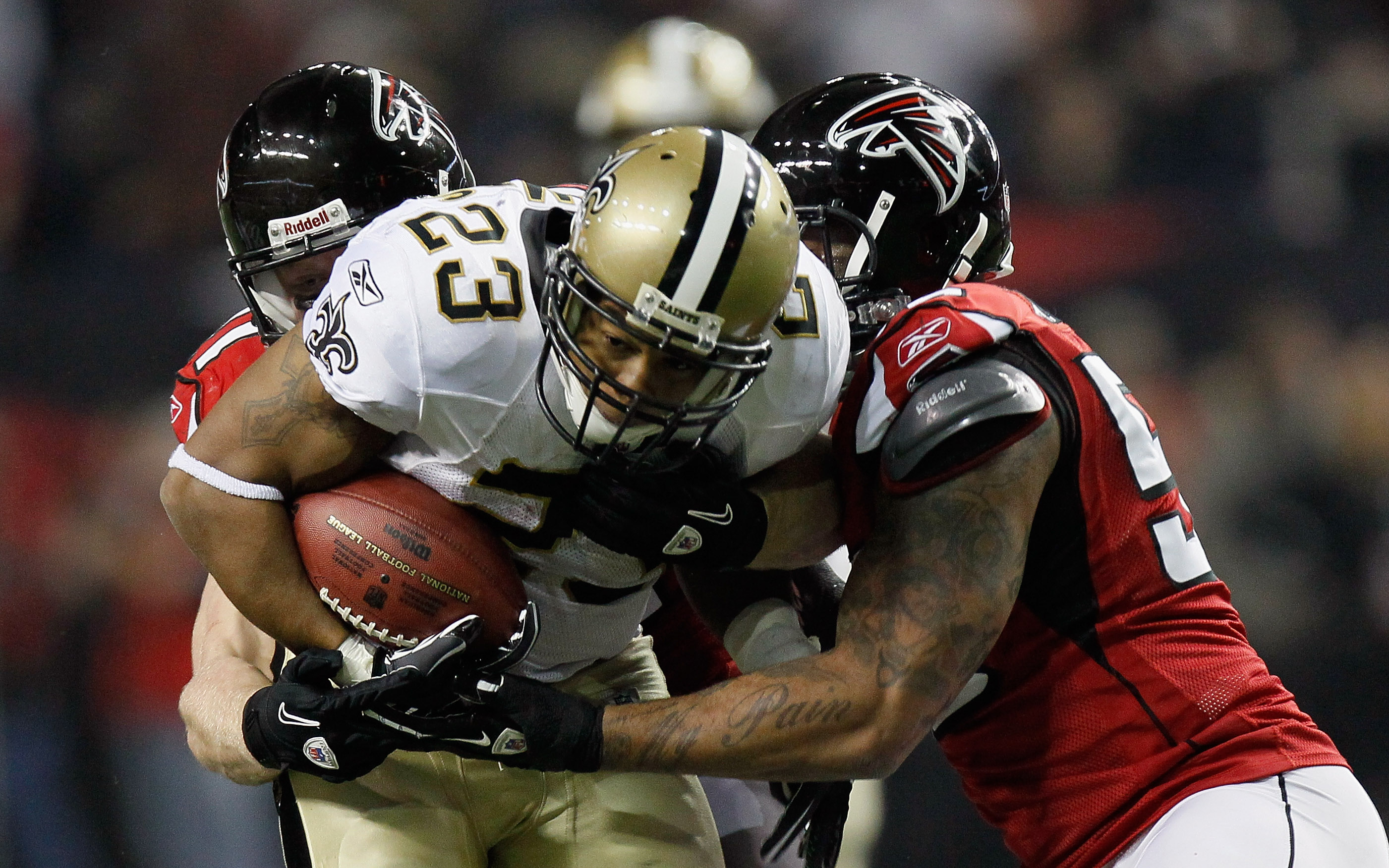 ATLANTA, GA - DECEMBER 27:  Pierre Thomas #23 of the New Orleans Saints fights off two defenders in the first half during the game against the Atlanta Falcons at the Georgia Dome on December 27, 2010 in Atlanta, Georgia.  (Photo by Kevin C. Cox/Getty Imag