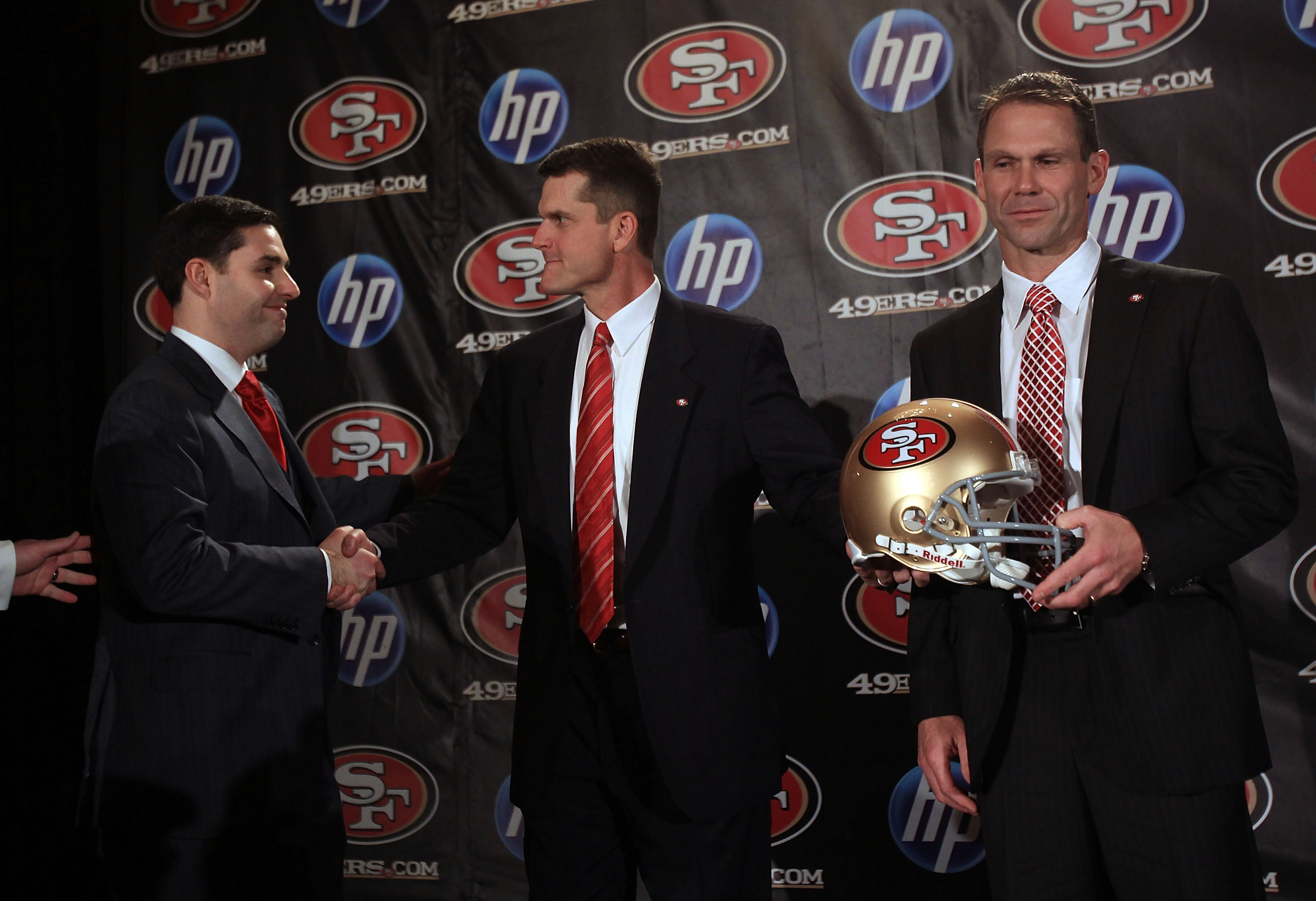 SAN FRANCISCO, CA - JANUARY 07:  Jim Harbaugh shakes hands with President and CEO of the San Francisco 49ers, Jed York, while general manager Trent Baalk holds a 49ers helmet following a press conference where Harbaugh was introduced as the new San Franci