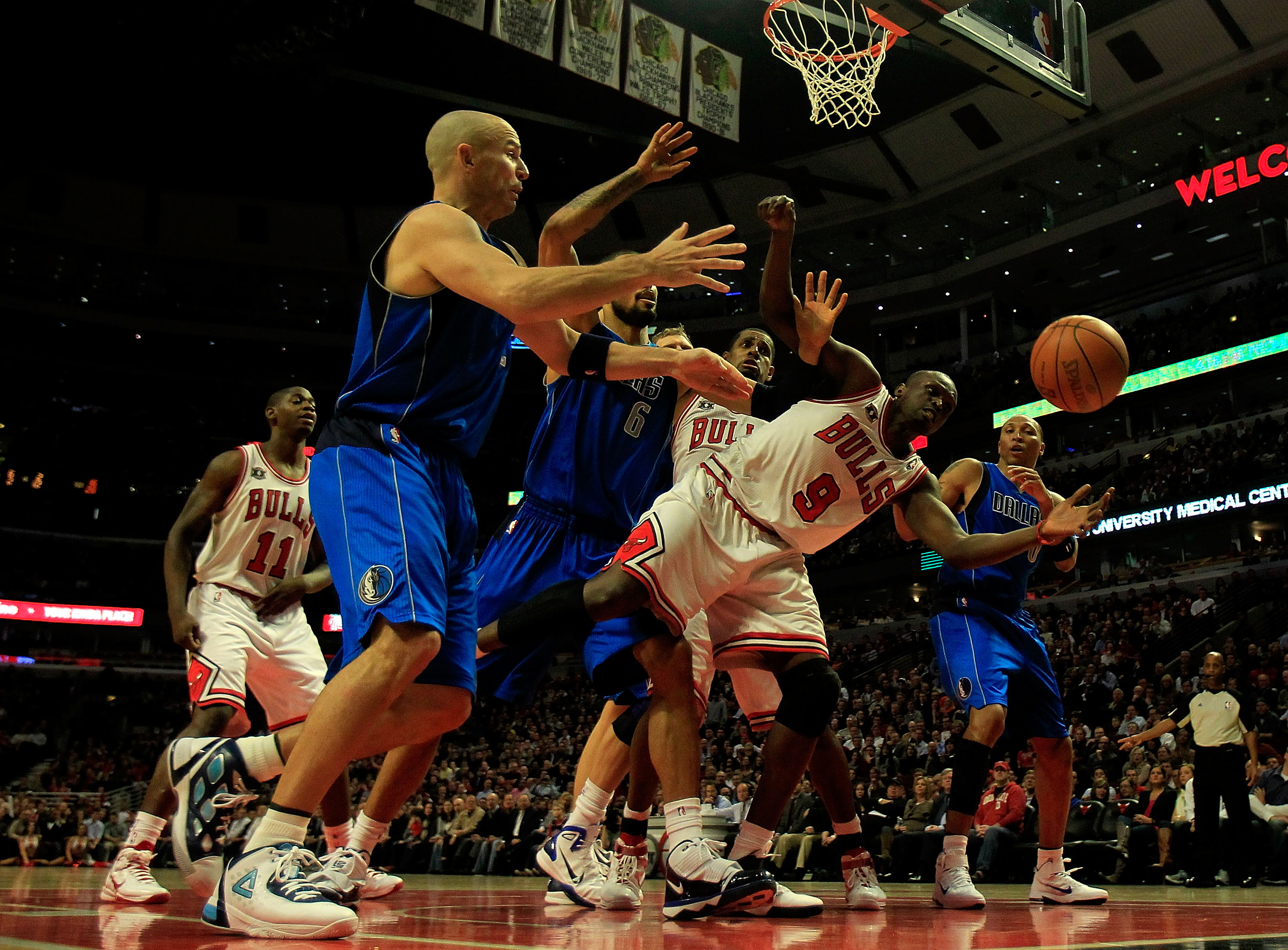 CHICAGO, IL - JANUARY 20: Loul Deng #9 of the Chicago Bulls reaches for the ball under pressure from Tyson Chandler #6 and Jason Kidd #2 of the Dallas Mavericks at the United Center on January 20, 2011 in Chicago, Illinois. The Bulls defeated the Maverick
