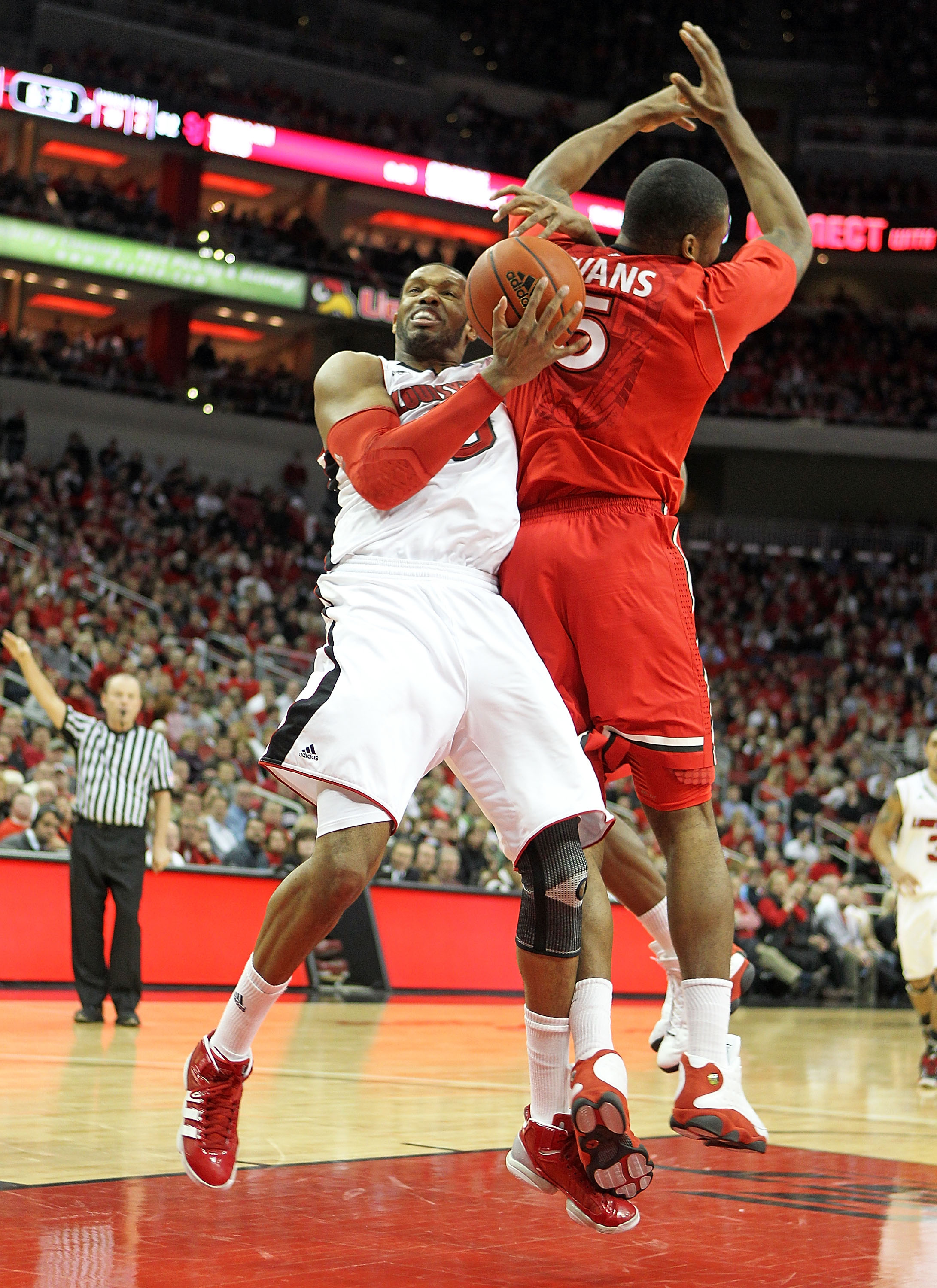 LOUISVILLE, KY - JANUARY 19: George Goode #0 of the Louisville Cardinals and Sean Evans #5 of the St. John's Red Storm battle for a rebound during the Big East Conference game at the KFC Yum! Center on January 19, 2011 in Louisville, Kentucky.  Louisville