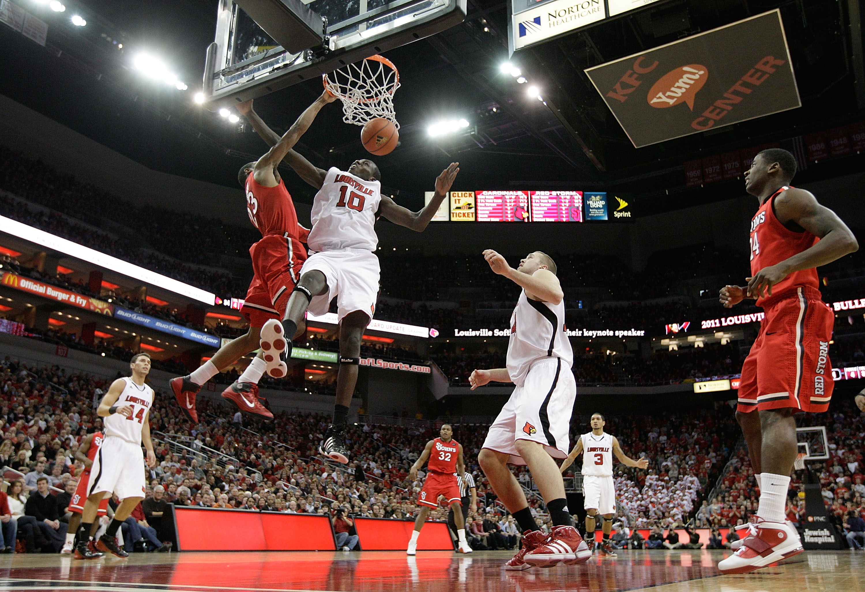 LOUISVILLE, KY - JANUARY 19:   Paris Horne #23 of the St. John's Red Storm dunks the ball while defended by Gorgui Deng #10 of the Louisville Cardinals during the Big East Conference game  at the KFC Yum! Center on January 19, 2011 in Louisville, Kentucky