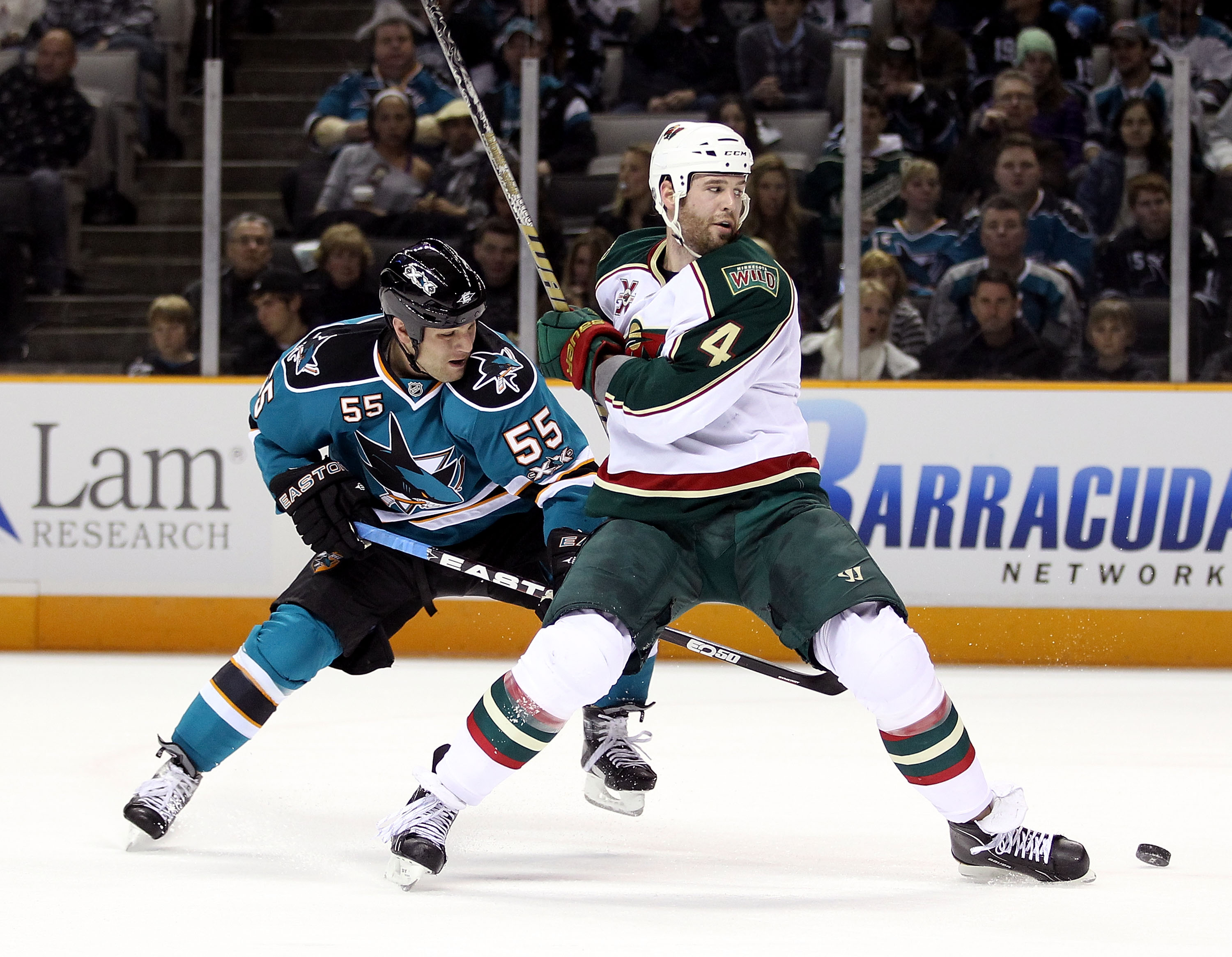SAN JOSE, CA - JANUARY 22:  Ben Eager #55 of the San Jose Sharks and Clayton Stoner #4 of the Minnesota Wild go for the puck at HP Pavilion on January 22, 2011 in San Jose, California.  (Photo by Ezra Shaw/Getty Images)