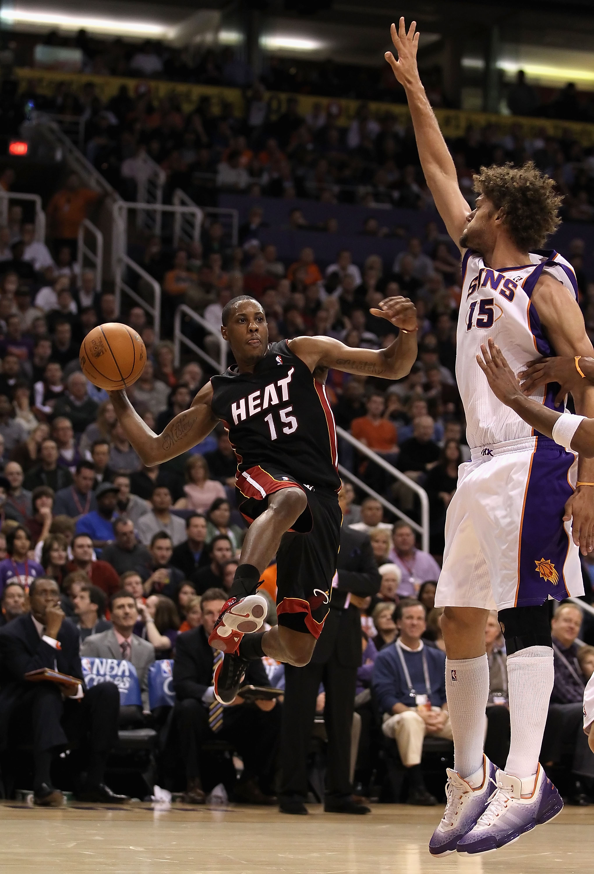 PHOENIX - DECEMBER 23:  Mario Chalmers #15 of the Miami Heat passes the ball around Robin Lopez #15 of the Phoenix Suns during the NBA game at US Airways Center on December 23, 2010 in Phoenix, Arizona. The Heat defeated the Suns 95-83.  NOTE TO USER: Use