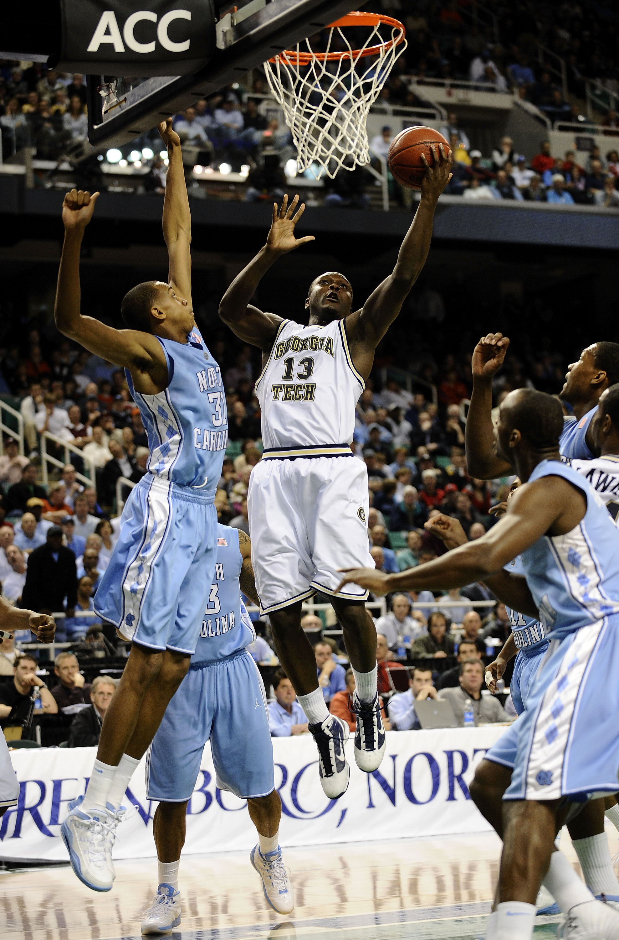 GREENSBORO, NC - MARCH 11:  D'Andre Bell #13 of the Georgia Tech Yellow Jackets drive to the hoop by John Henson #31 of the University of the North Carolina Tarheels in their first round game in the 2010 ACC Men's Basketball Tournament at the Greensboro C