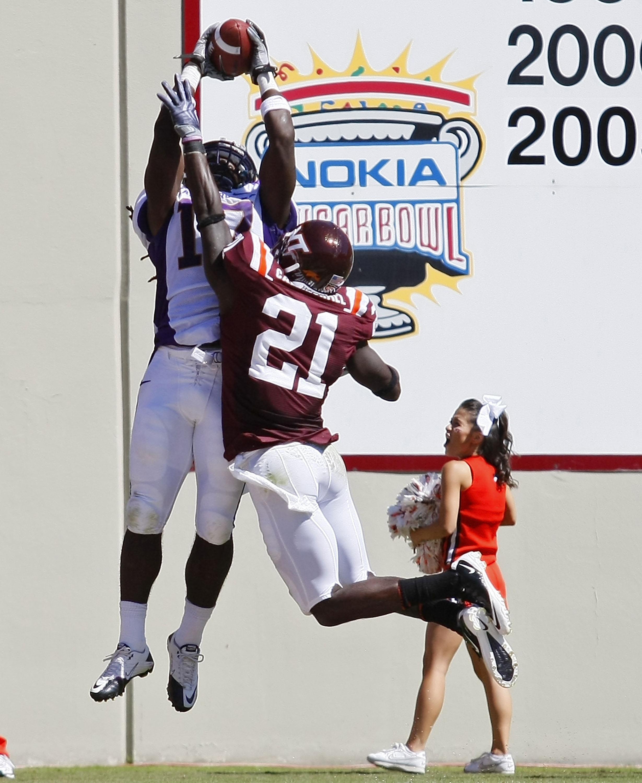 BLACKSBURG, VA - SEPTEMBER 18:  Wide receiver Dwayne Harris #17 of the East Carolina Pirates leaps to catch a pass for a touchdown over cornerback Rashad Carmichael #21 of the Virginia Tech Hokies at Lane Stadium on September 18, 2010 in Blacksburg, Virgi