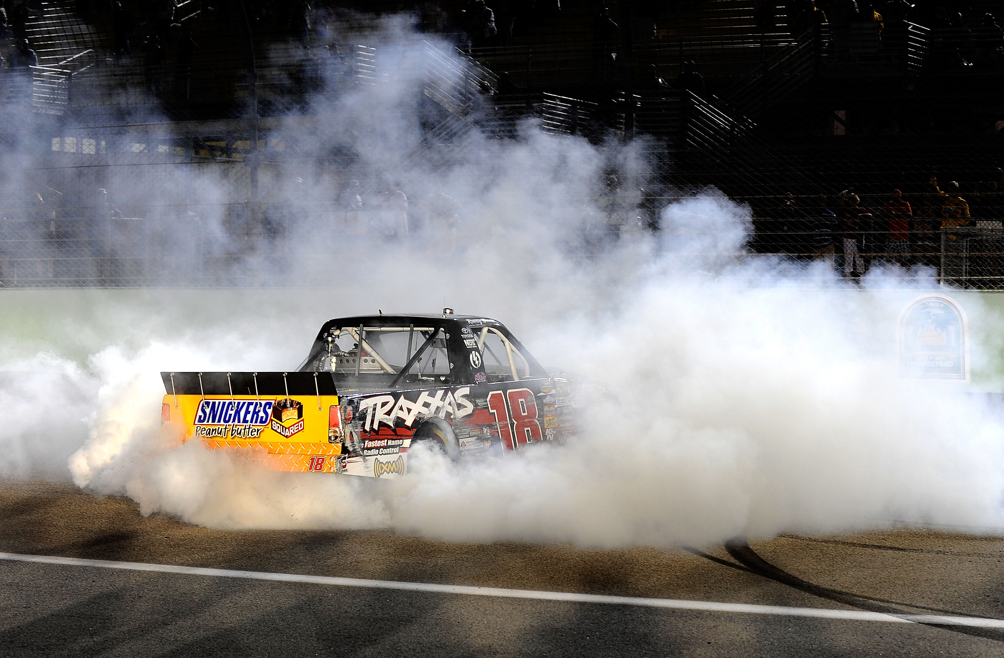 HOMESTEAD, FL - NOVEMBER 19:  Kyle Busch, driver of the #18 Toyota Tundra/TRAXXAS Toyota, celebrates with a burnout after winning the NASCAR Camping World Truck Series Ford 200 at Homestead-Miami Speedway on November 19, 2010 in Homestead, Florida.  (Phot