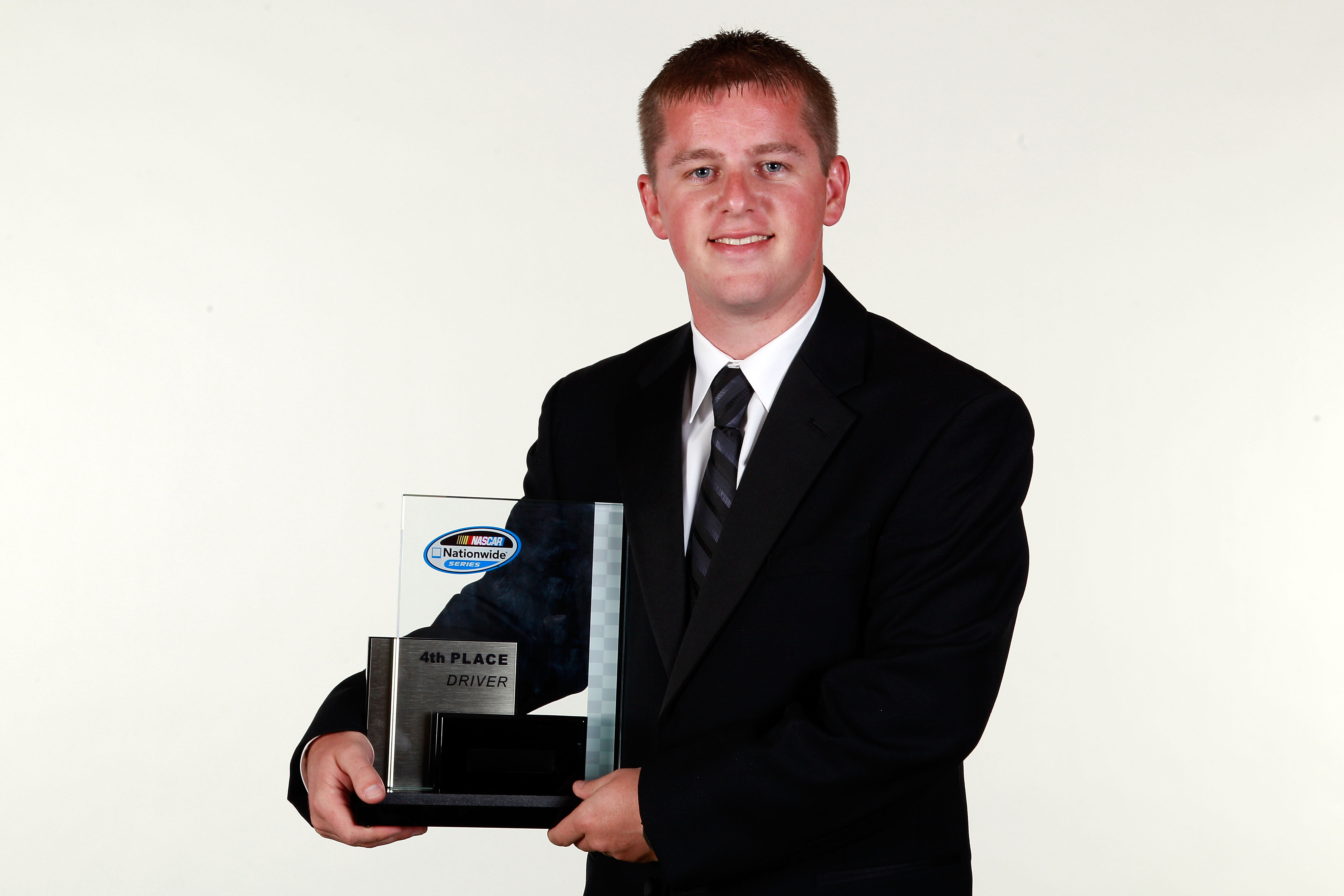 MIAMI - NOVEMBER 22:  Justin Allgaier, driver of the #12 Verizon Wireless Dodge, poses with the 4th place Nationwide Series trophy during the NASCAR Nationwide/Camping World Truck Series Banquet at Loews Miami Beach Hotel on November 22, 2010 in Miami, Fl