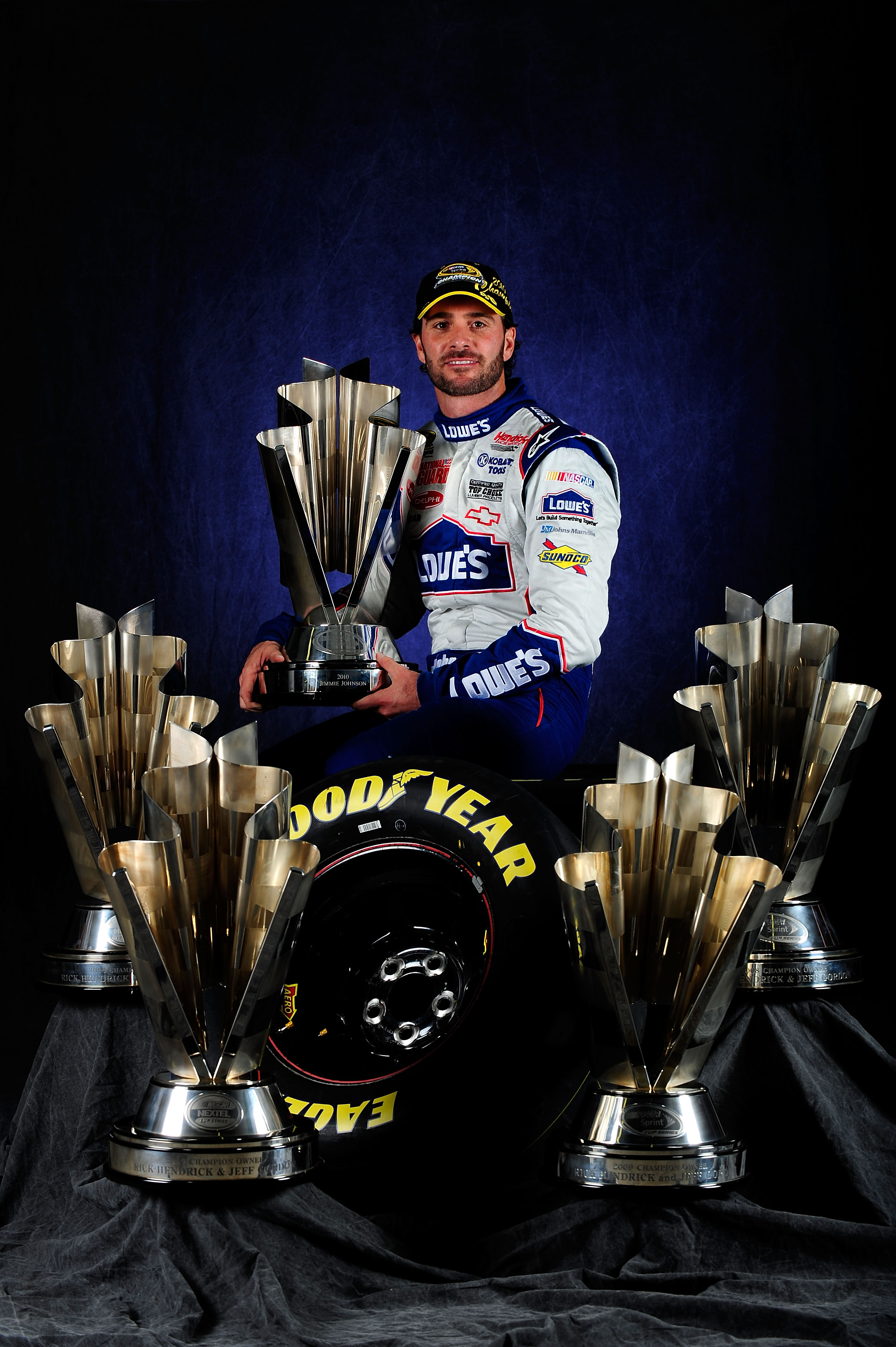 HOMESTEAD, FL - NOVEMBER 21:  NASCAR Champion Jimmie Johnson, driver of the #48 Lowe's Chevrolet, poses with the Sprint Cup Series Championship trophies at Homestead-Miami Speedway on November 21, 2010 in Homestead, Florida. Johnson clinched his fifth str