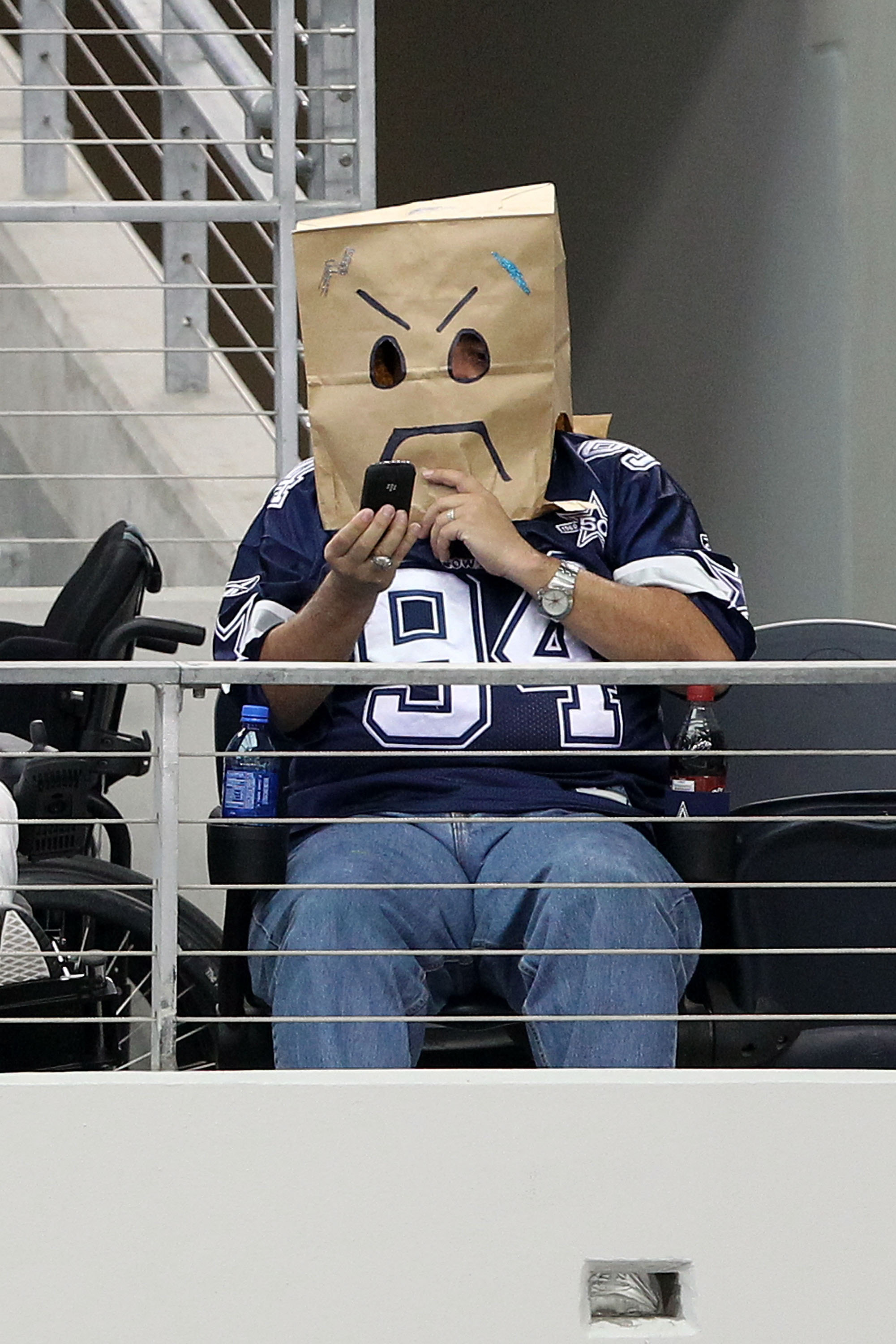 ARLINGTON, TX - OCTOBER 31:  A fan of the Dallas Cowboys wears a brown paper bag on his  head as he looks at his phone against the Jacksonville Jaguars at Cowboys Stadium on October 31, 2010 in Arlington, Texas.  (Photo by Chris Chambers/Getty Images)
