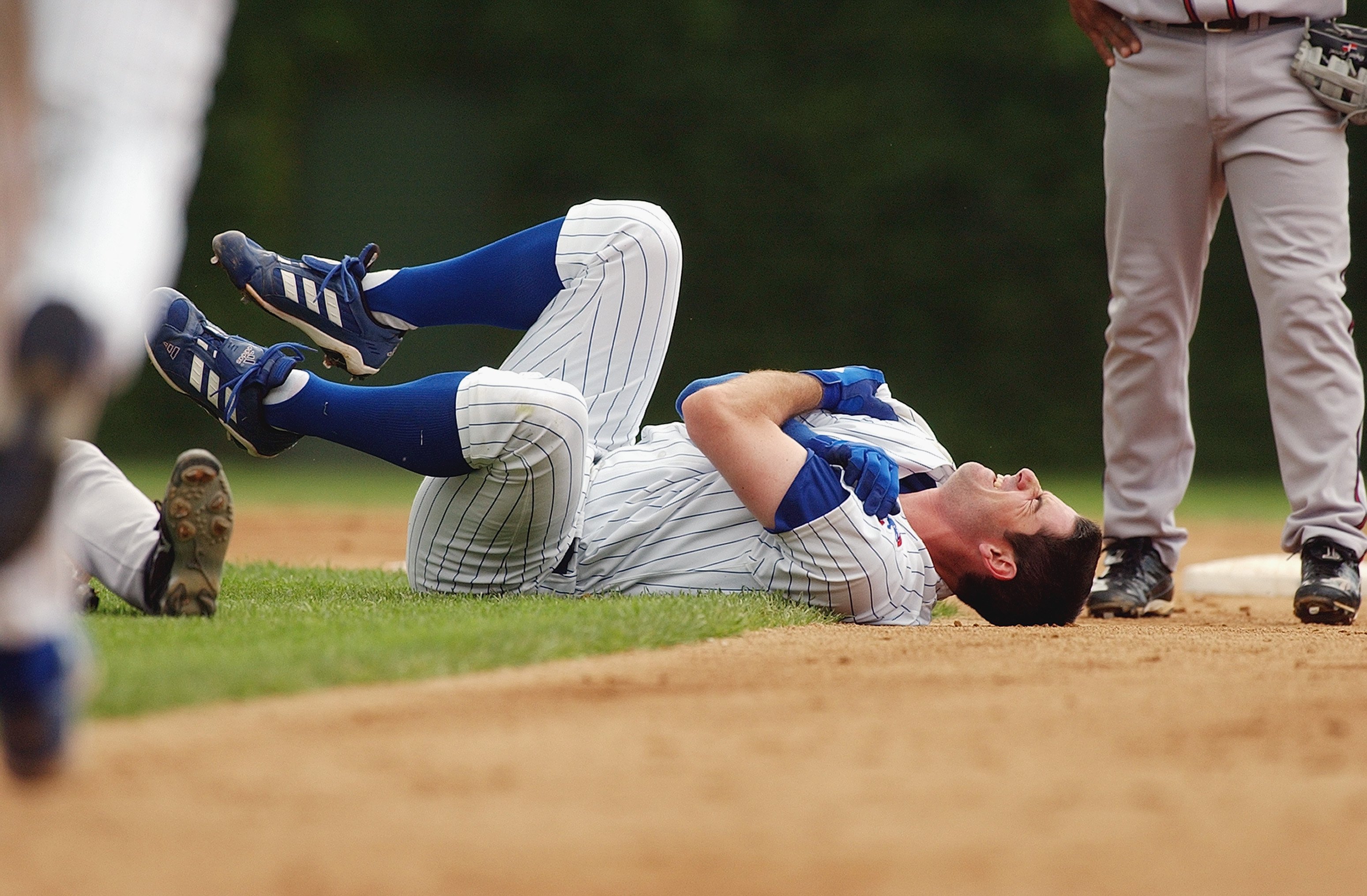 CHICAGO - JULY 11:  Starting pitcher Mark Prior #22 of the Chicago Cubs grabs his shoulder in pain after colliding with second baseman Marcus Giles #22 of the Atlanta Braves during the second inning of the game at Wrigley Field on July 11, 2003 in Chicago