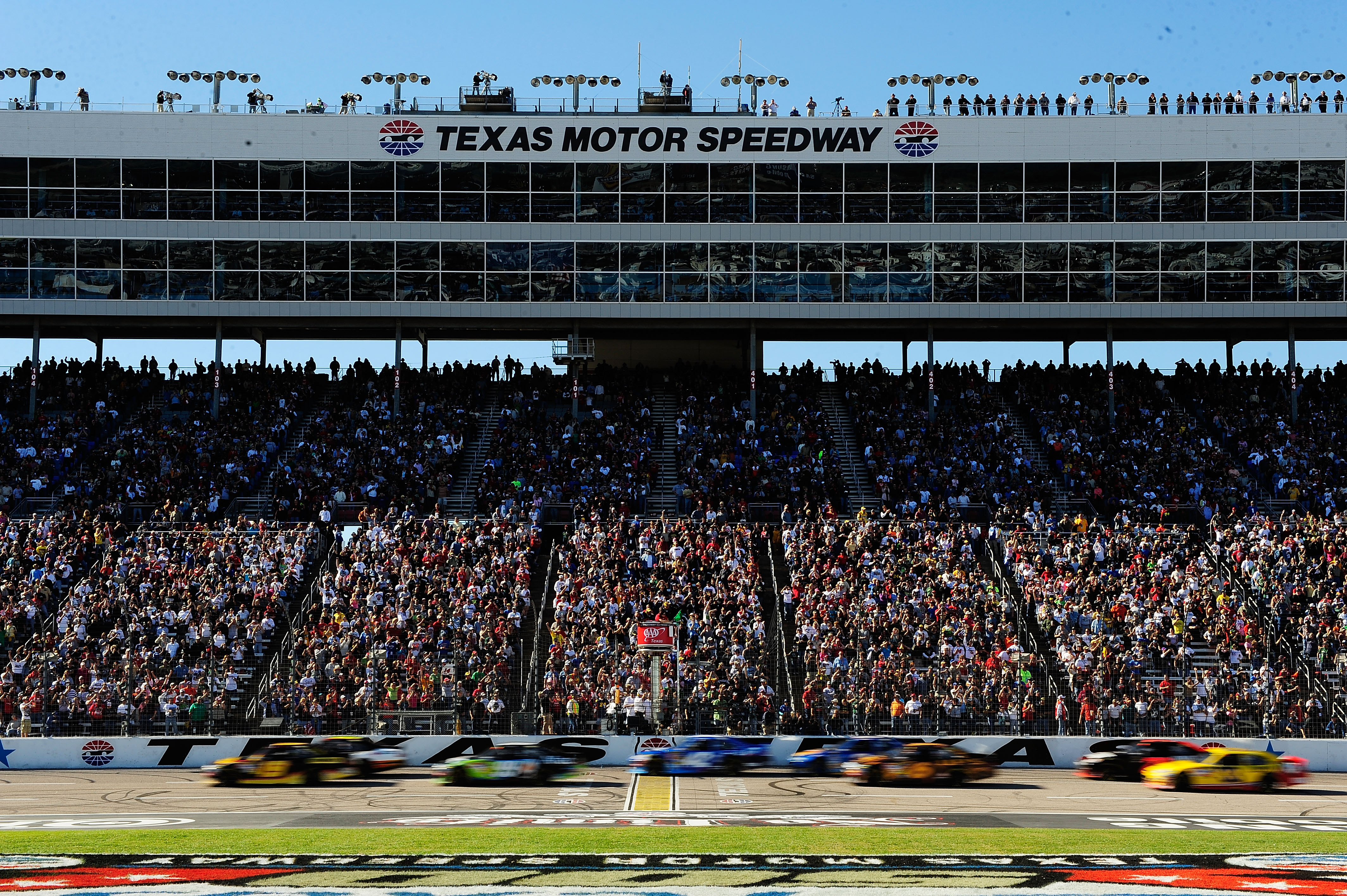 FORT WORTH, TX - NOVEMBER 07:  Elliott Sadler, driver of the #19 Stanley Ford, and Greg Biffle, driver of the #16 American Red Cross Ford, lead the field to the green flag to start the NASCAR Sprint Cup Series AAA Texas 500 at Texas Motor Speedway on Nove