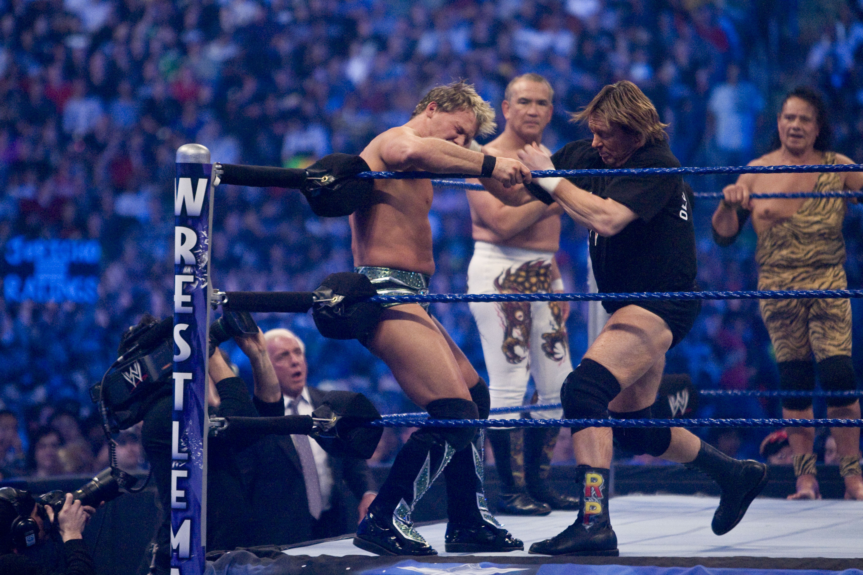 HOUSTON, TX - APRIL 5:  (L-R) Former professional wrestlers Ric Flair (seen outside the ring) looks on as WWE Superstar Chris Jericho gets pummeled on the ropes by 'Rowdy' Roddy Piper. Ricky 'The Dragon' Steamboat and Jimmy 'Superfly' Snuka look on during