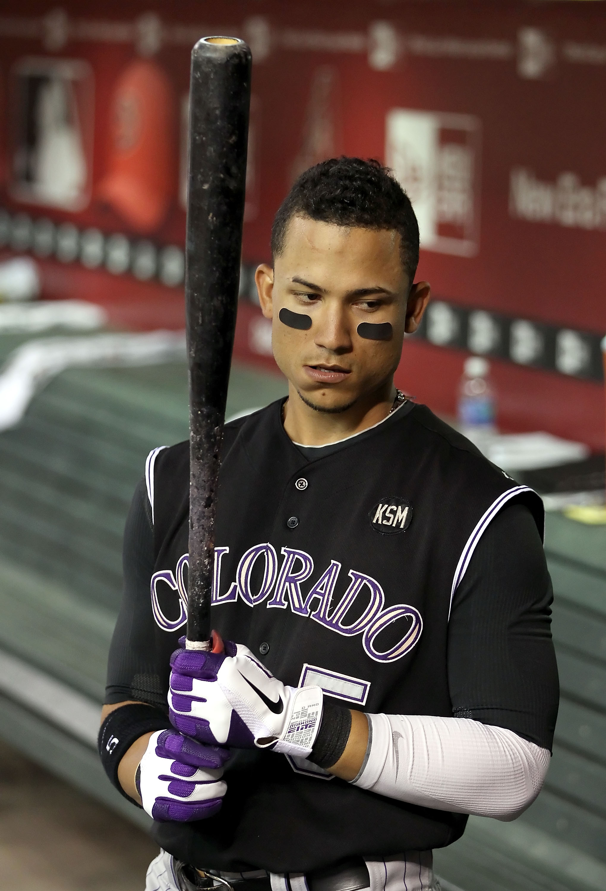 PHOENIX - SEPTEMBER 22:  Carlos Gonzalez #5 of the Colorado Rockies warms up in the dugout during the Major League Baseball game against the Arizona Diamondbacks at Chase Field on September 22, 2010 in Phoenix, Arizona.  (Photo by Christian Petersen/Getty
