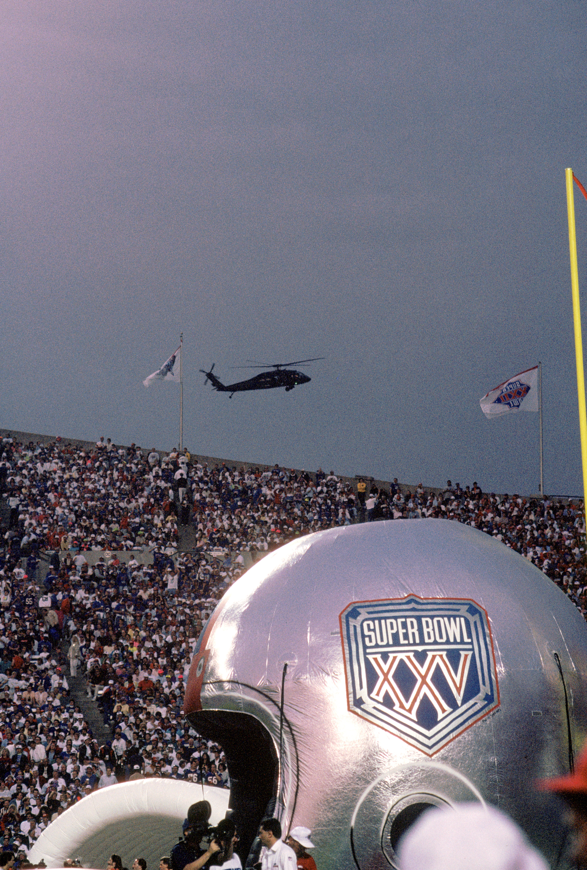 TAMPA, FL - JANUARY 27:  General view of the Super Bowl XXV logo on an inflatable helmet as a military helicopter patrols the air space above Tampa Stadium looking for terrorist prior to Super Bowl XXV between the Buffalo Bills and the New York Giants at