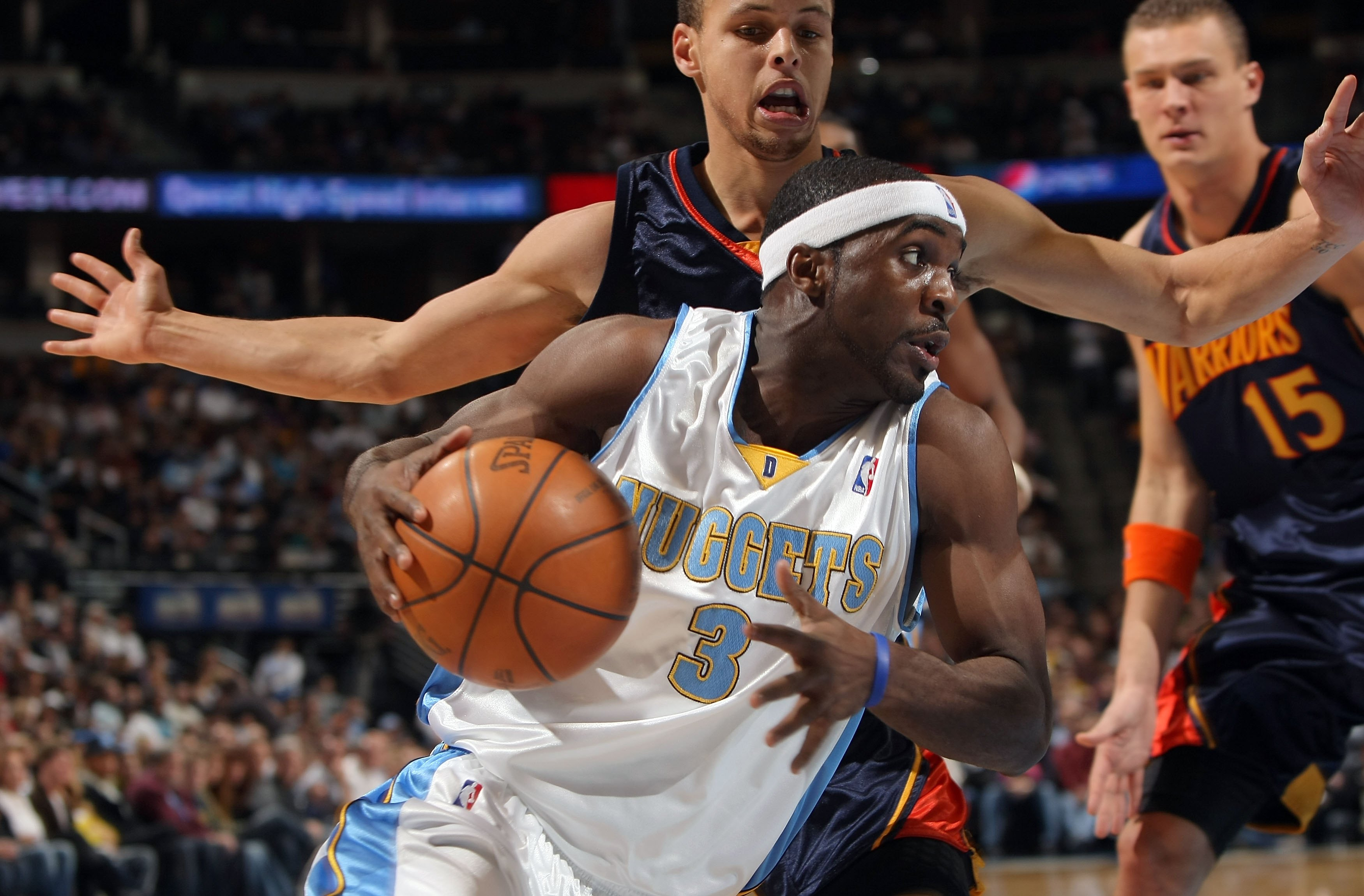 DENVER - JANUARY 05:  Ty Lawson #3 of the Denver Nuggets drives the ball past Stephen Curry #30 and Andris Biedrins #15 of the Golden State Warriors at the Pepsi Center on January 5, 2010 in Denver, Colorado. The Nuggets defeated the Warriors 123-122. NOT