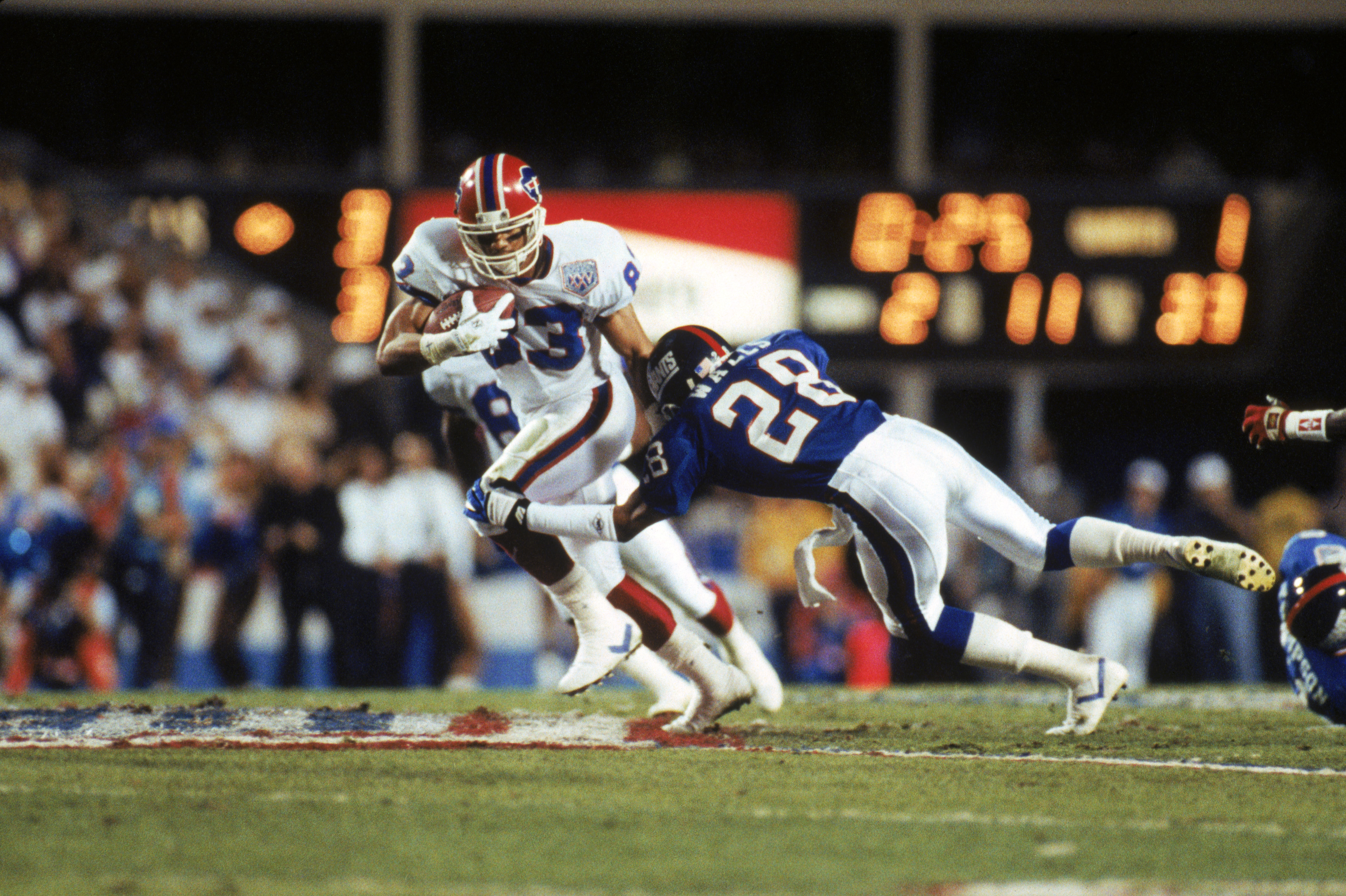 TAMPA, FL - JANUARY 27:  Wide receiver Andre Reed #83 of the Buffalo Bills tries to break away from a tackle by cornerback Everson Walls #28 of the New York Giants on a twenty yard pass in Super Bowl XXV at Tampa Stadium on January 27, 1991 in Tampa, Flor