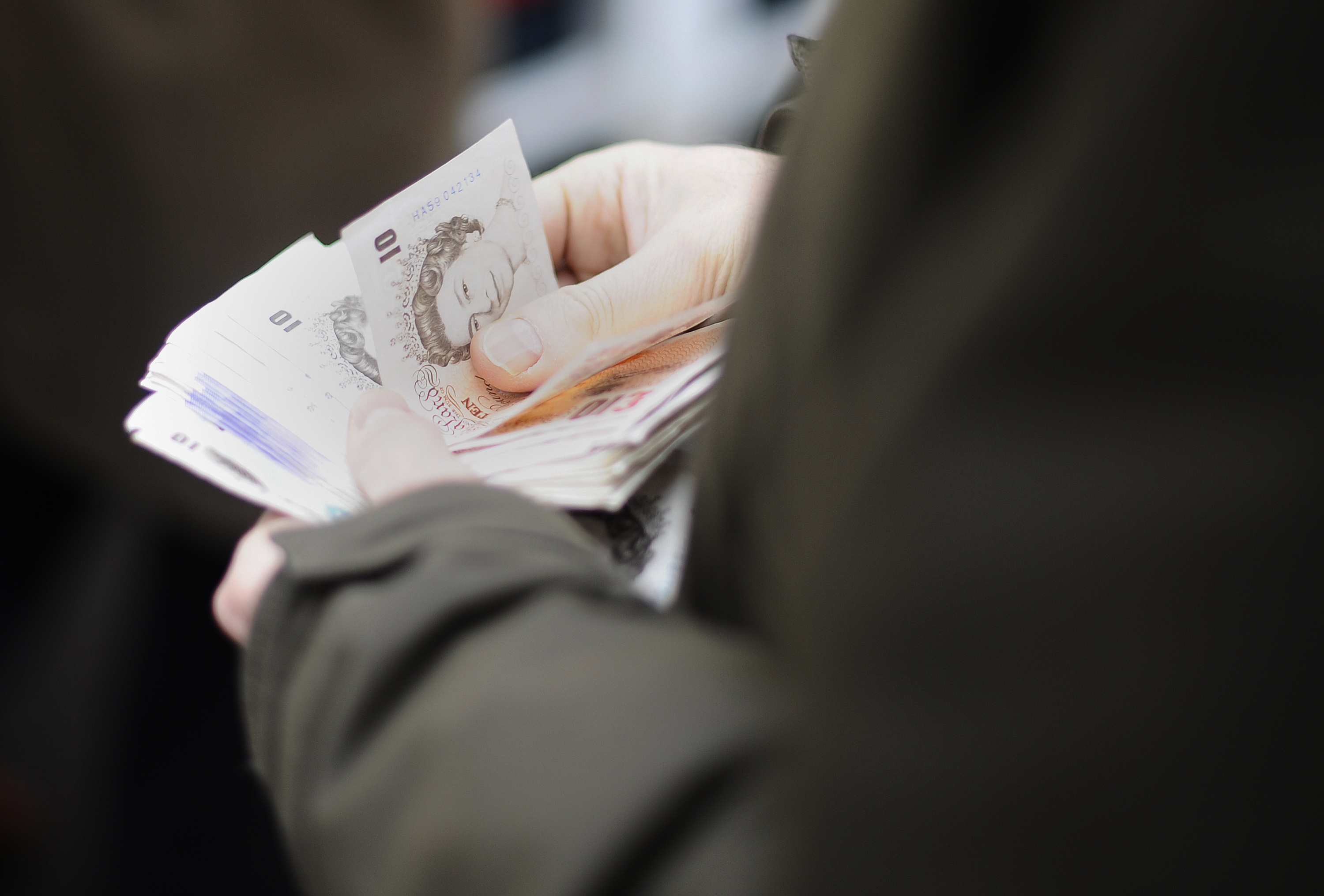 NEWBURY, ENGLAND - DECEMBER 15:  A punter gets his money ready for a wager at Newbury racecourse on December 15, 2010 in Newbury, England.  (Photo by Alan Crowhurst/ Getty Images)