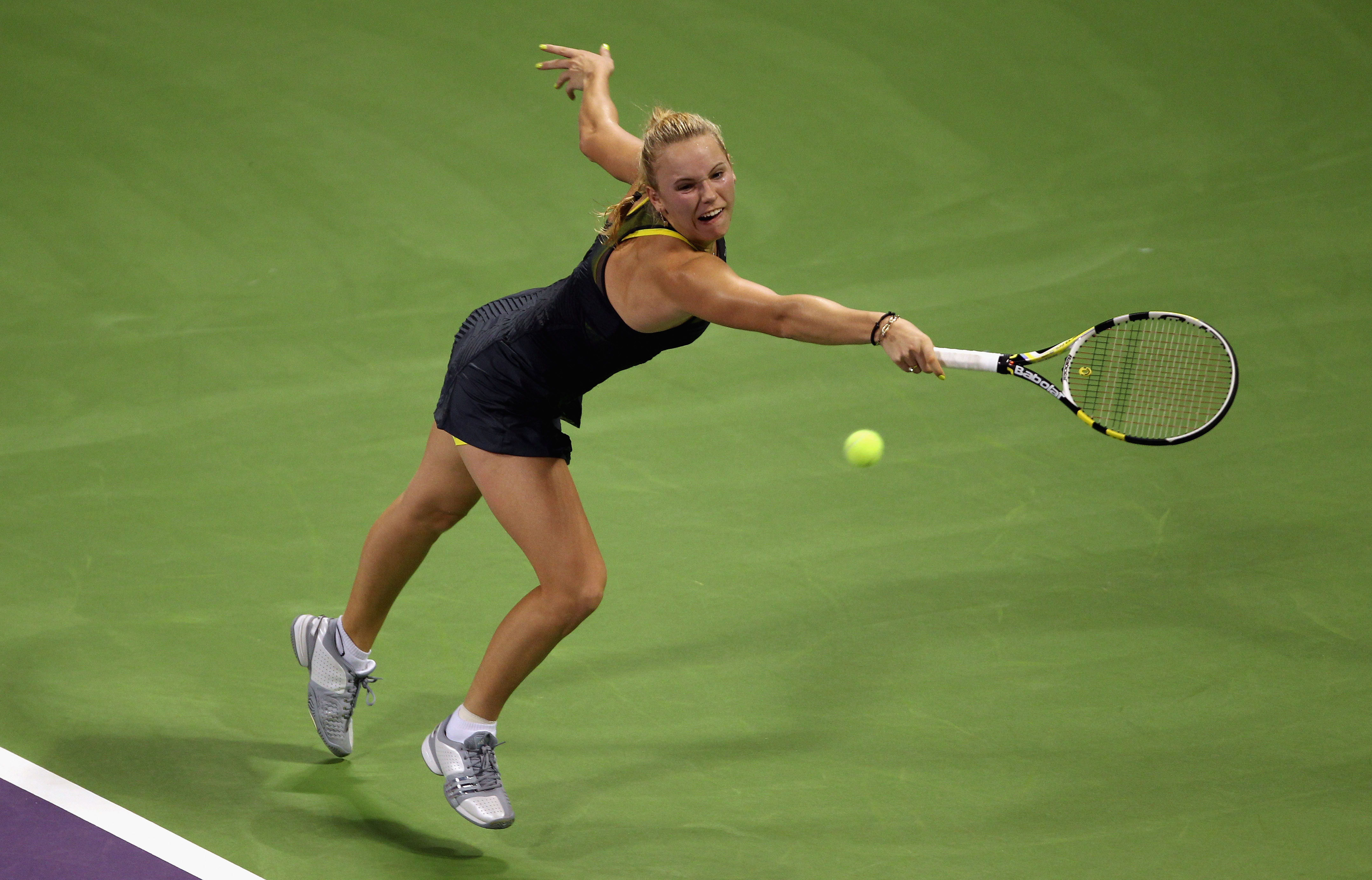 DOHA, QATAR - OCTOBER 30:  Caroline Wozniacki of Denmark returns a shot to Vera Zvonareva of Russia on day five of the WTA Championships at the Khalifa Tennis Complex on October 30, 2010 in Doha, Qatar.  (Photo by Bryn Lennon/Getty Images)