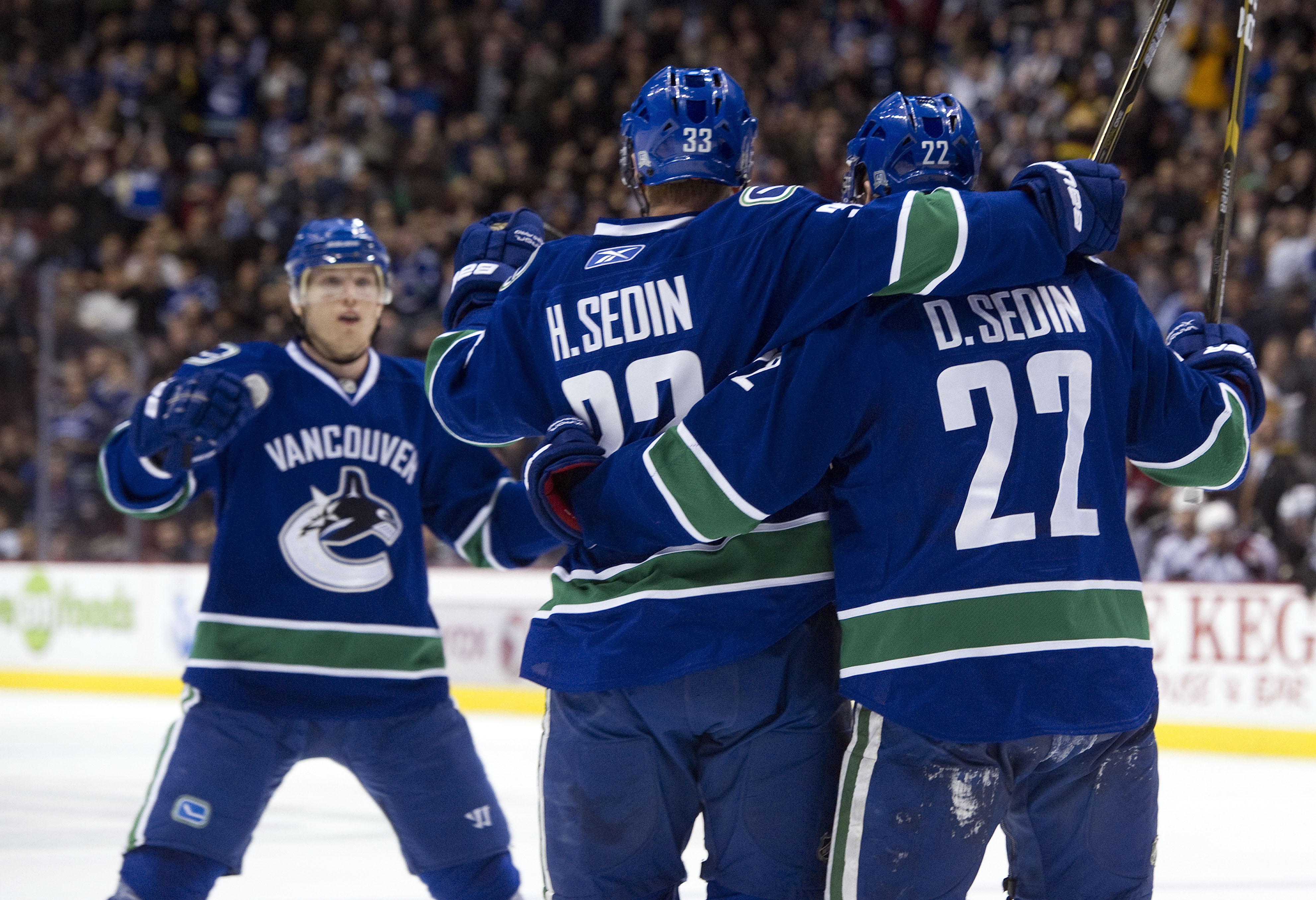 VANCOUVER, CANADA - NOVEMBER 24: Daniel Sedin #22 celebrates with brother Henrik Sedin #33 and Christian Ehrhoff #5 of the Vancouver Canucks after scoring against the Colorado Avalanche during the second period in NHL action on November 24, 2010 at Rogers
