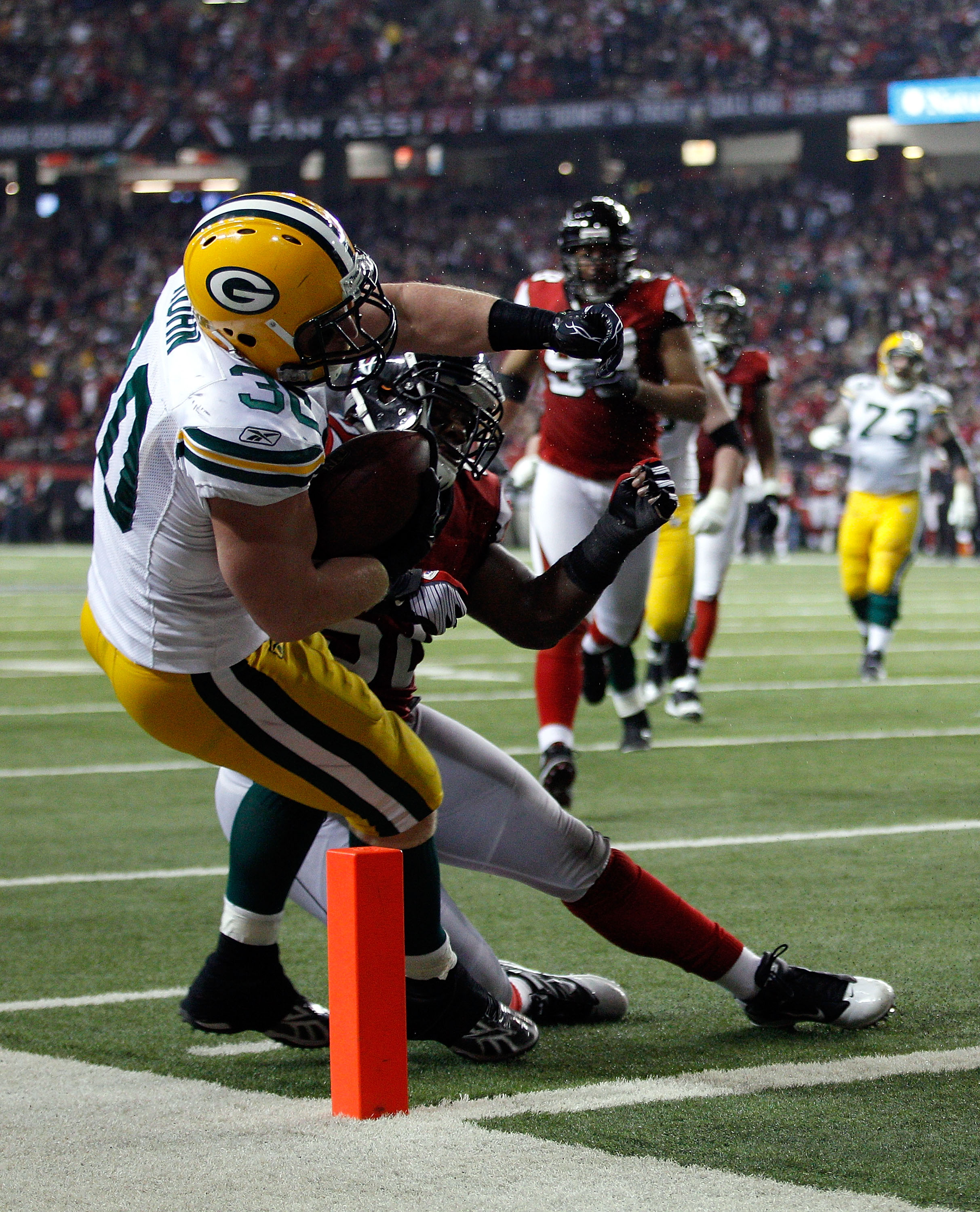ATLANTA, GA - JANUARY 15:  John Kuhn #30 of the Green Bay Packers scores a 7-yard touchdown reception against the Atlanta Falcons during their 2011 NFC divisional playoff game at Georgia Dome on January 15, 2011 in Atlanta, Georgia.  (Photo by Chris Grayt