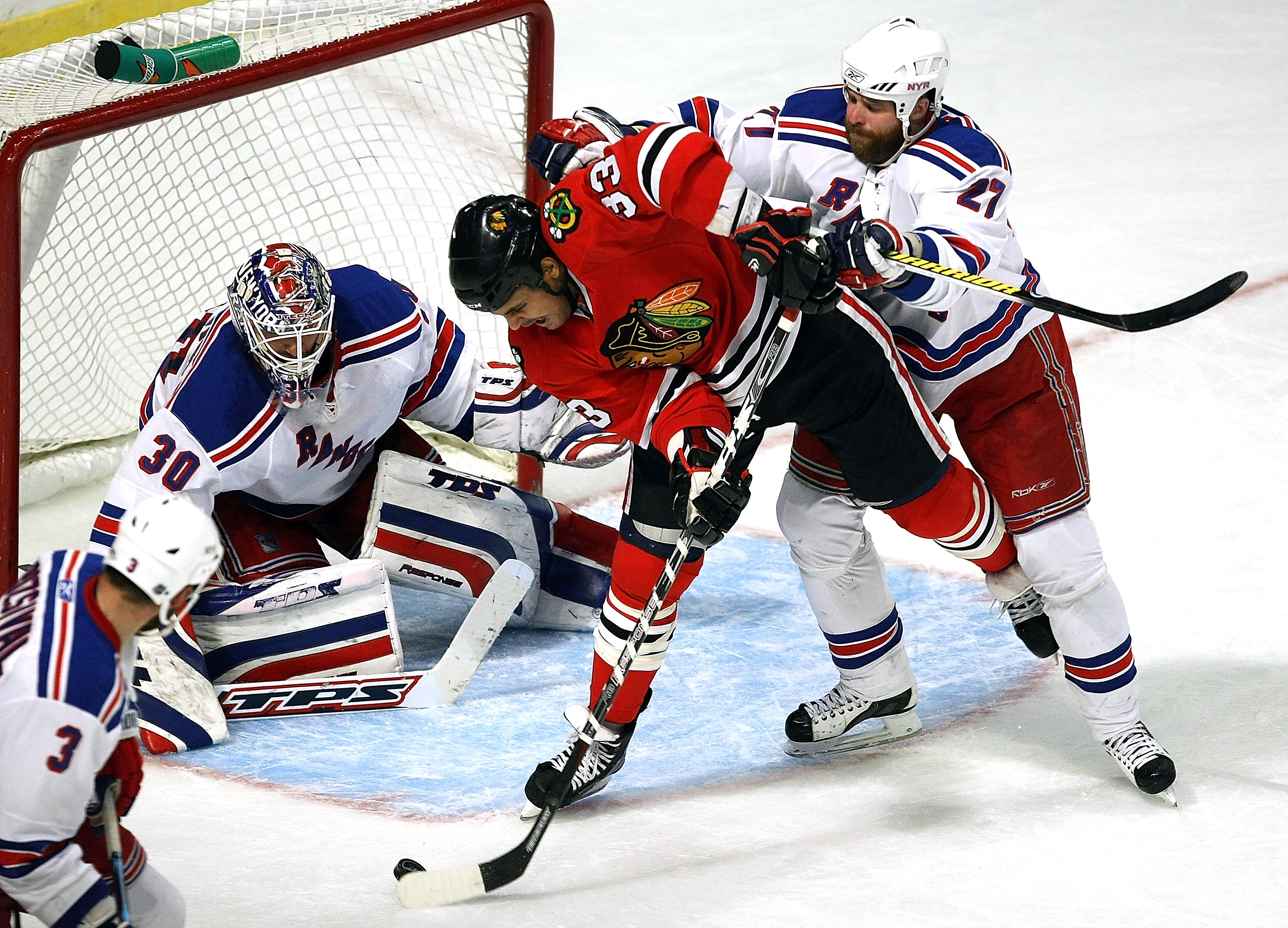 CHICAGO - JANUARY 16: Dustin Byfuglien #33 of the Chicago Blackhawks attempts a shot against Henrik Lundqvist #30 of the New York Rangers as defenseman Paul Mara #27 pushes him on January 16, 2009 at the United Center in Chicago, Illinois. The Rangers def