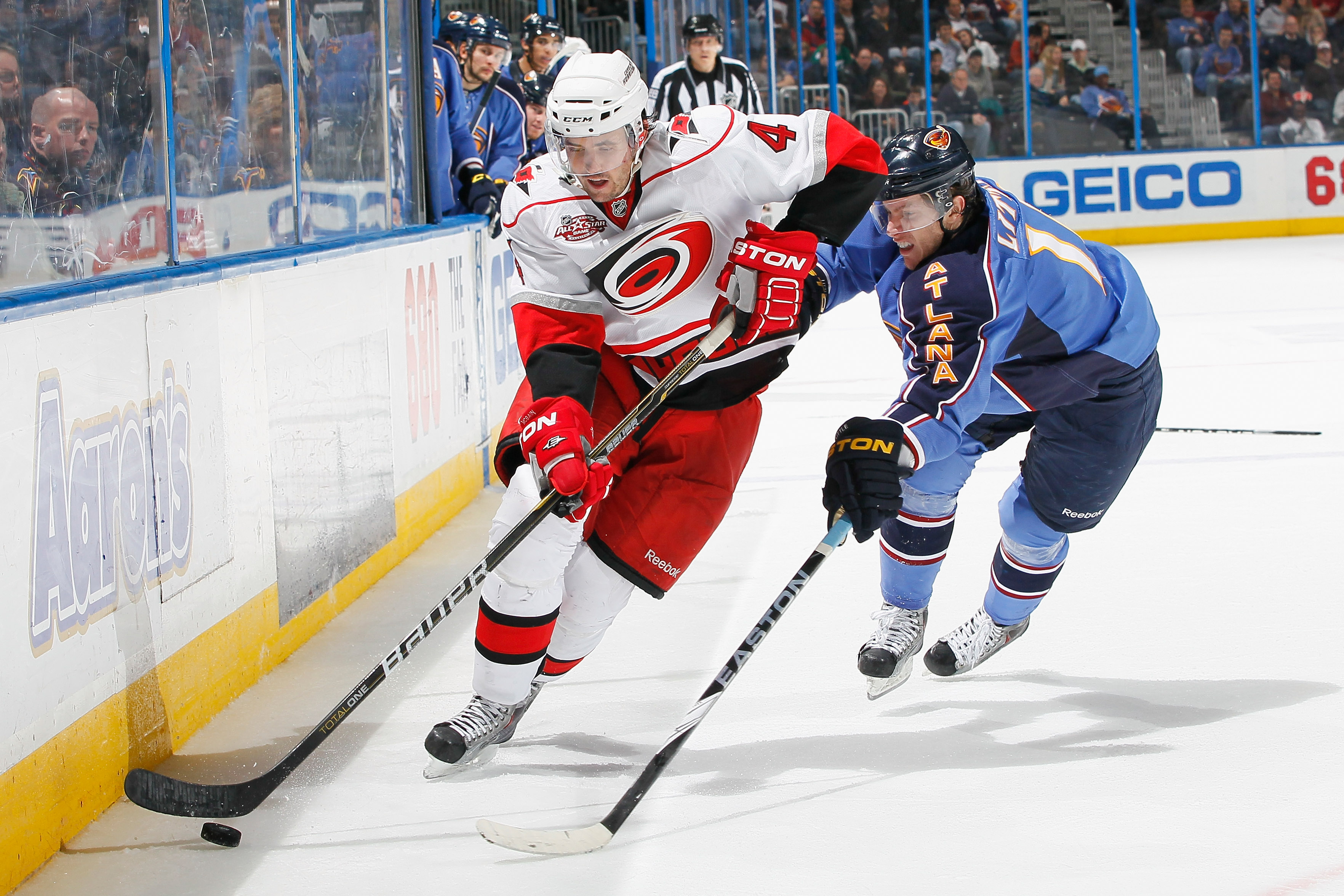 ATLANTA, GA - DECEMBER 16:  Jamie McBain #4 of the Carolina Hurricanes pushes the puck up the ice against Bryan Little #10 of the Atlanta Thrashers at Philips Arena on December 16, 2010 in Atlanta, Georgia.  (Photo by Kevin C. Cox/Getty Images)
