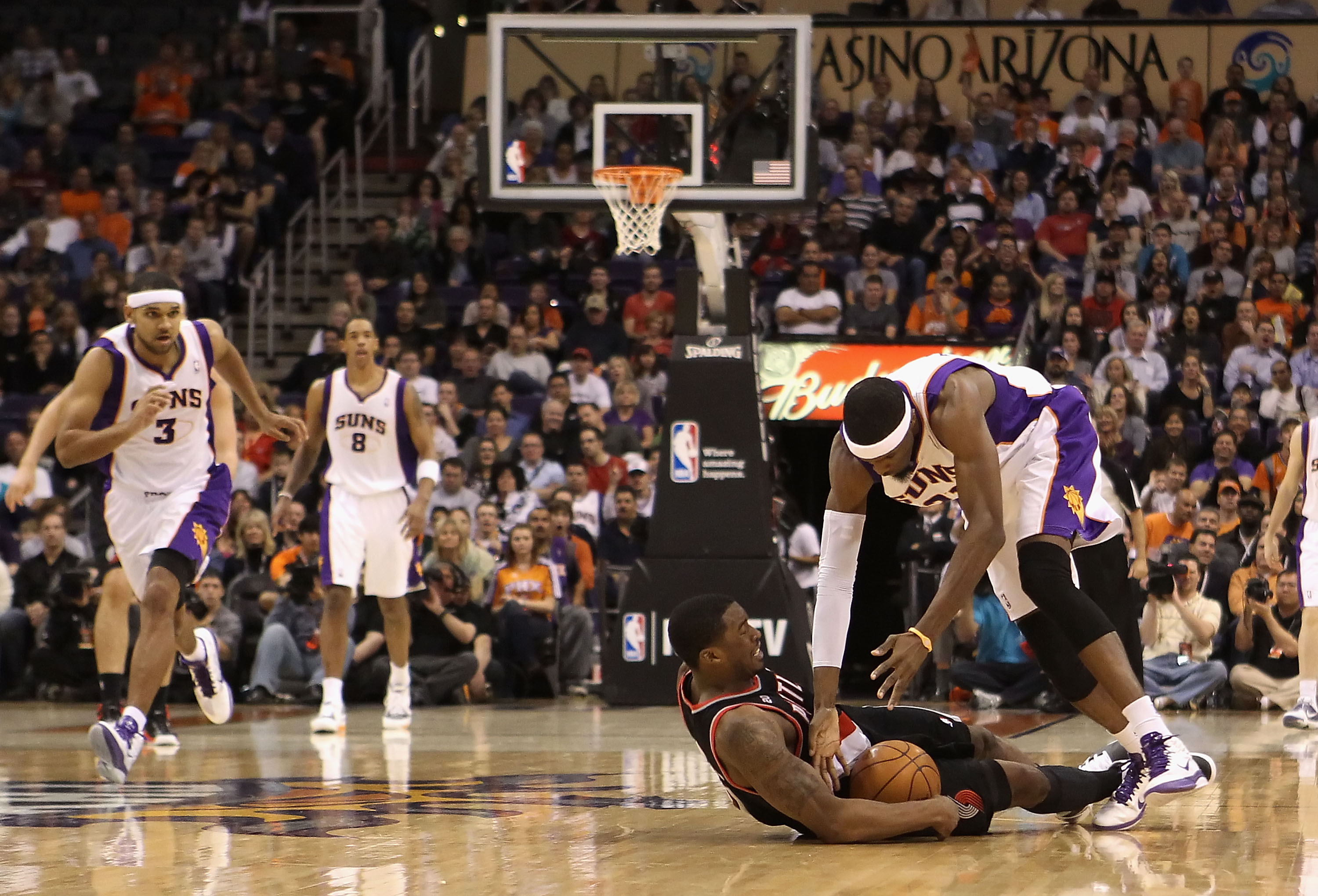 PHOENIX, AZ - JANUARY 14:  Hakim Warrick #21 of the Phoenix Suns dives for a loose ball with Wesley Matthews #2 of the Portland Trail Blazers during the NBA game at US Airways Center on January 14, 2011 in Phoenix, Arizona. The Suns defeated the Trail Bla
