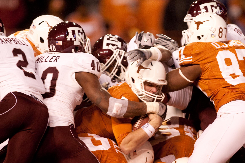 AUSTIN, TX - NOVEMBER 25:  University of Texas quarterback Garrett Gilbert #7 scores a touchdown during the second half against Texas A&M at Darrell K. Royal-Texas Memorial Stadium on November 25, 2010 in Austin, Texas. (Photo by Darren Carroll/Getty Imag