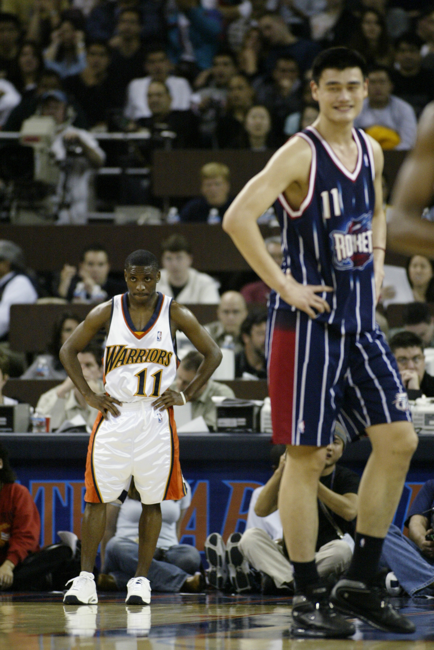 OAKLAND, CA - MARCH 21:  Earl Boykins #11 of the Golden State Warriors and Yao Ming #11 of the Houston Rockets rest during the game at The Arena in Oakland on March 21, 2003 in Oakland, California.  The Rockets won 117-107.  NOTE TO USER: User expressly a