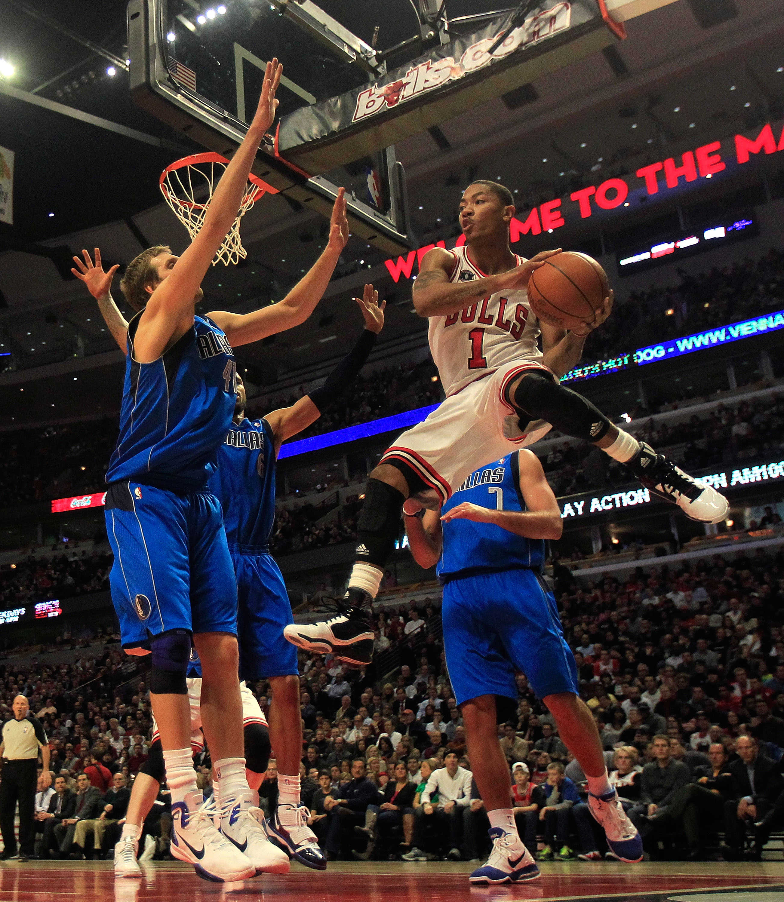 CHICAGO, IL - JANUARY 20: Derrick Rose #1 of the Chicago Bulls leaps to pass the ball around Dirk Nowitzki #41 of the Dallas Mavericks at the United Center on January 20, 2011 in Chicago, Illinois. The Bulls defeated the Mavericks 82-77. NOTE TO USER: Use