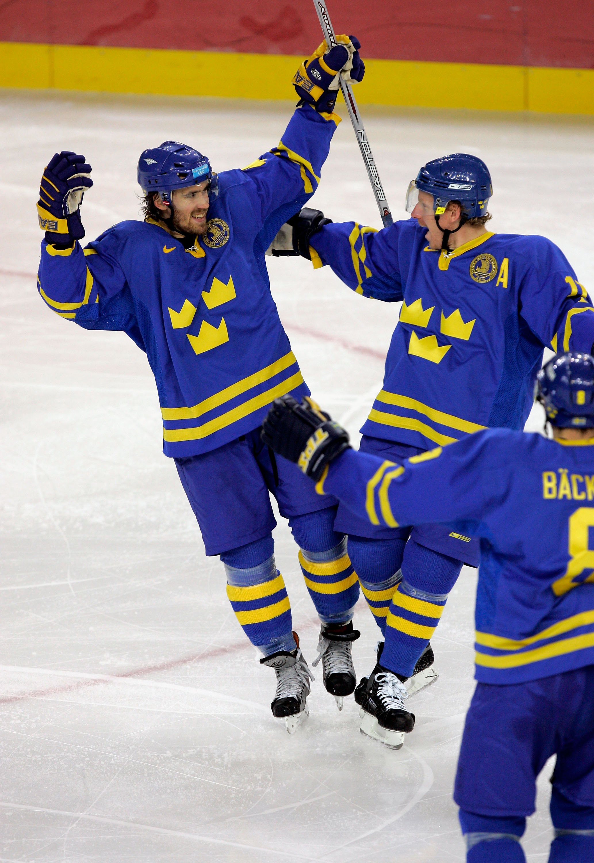 TURIN, ITALY - FEBRUARY 26:  Henrik Zetterberg #40 of Sweden is congratulated by teammates Daniel Alfredsson #11 and Christian Backman #8 after scoring in the second period to make the score 1-1 during the final of the men's ice hockey match between Finla