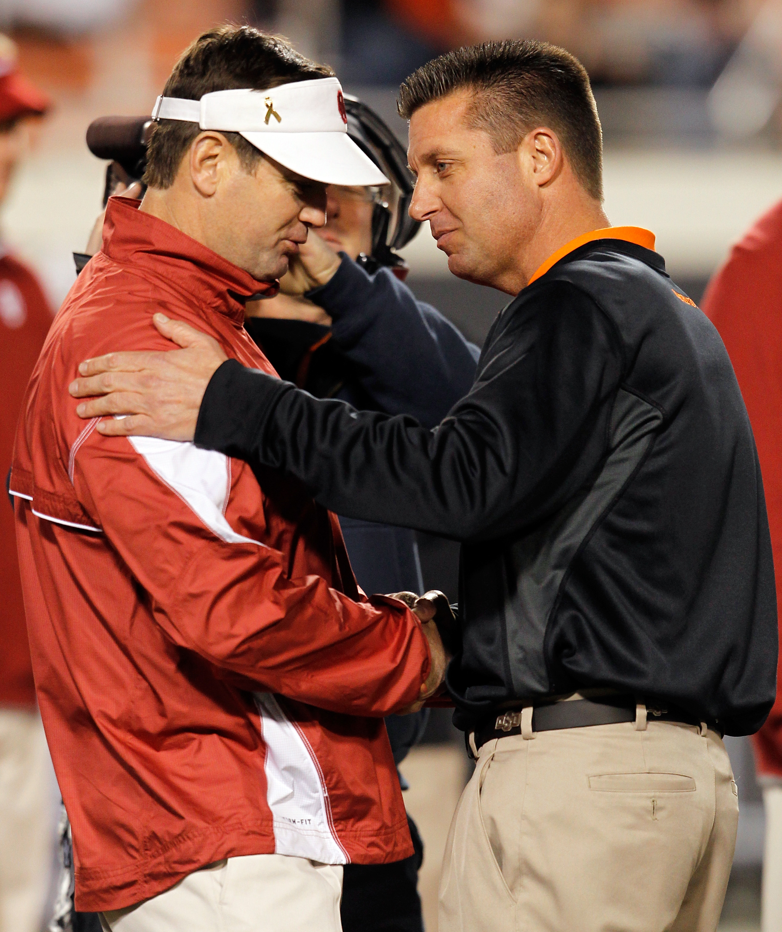 STILLWATER, OK - NOVEMBER 27:  Head coach Bob Stoops (L) of the Oklahoma Sooners talks with head coach Mike Gundy (R) of the Oklahoma State Cowboys at Boone Pickens Stadium on November 27, 2010 in Stillwater, Oklahoma.  (Photo by Tom Pennington/Getty Imag