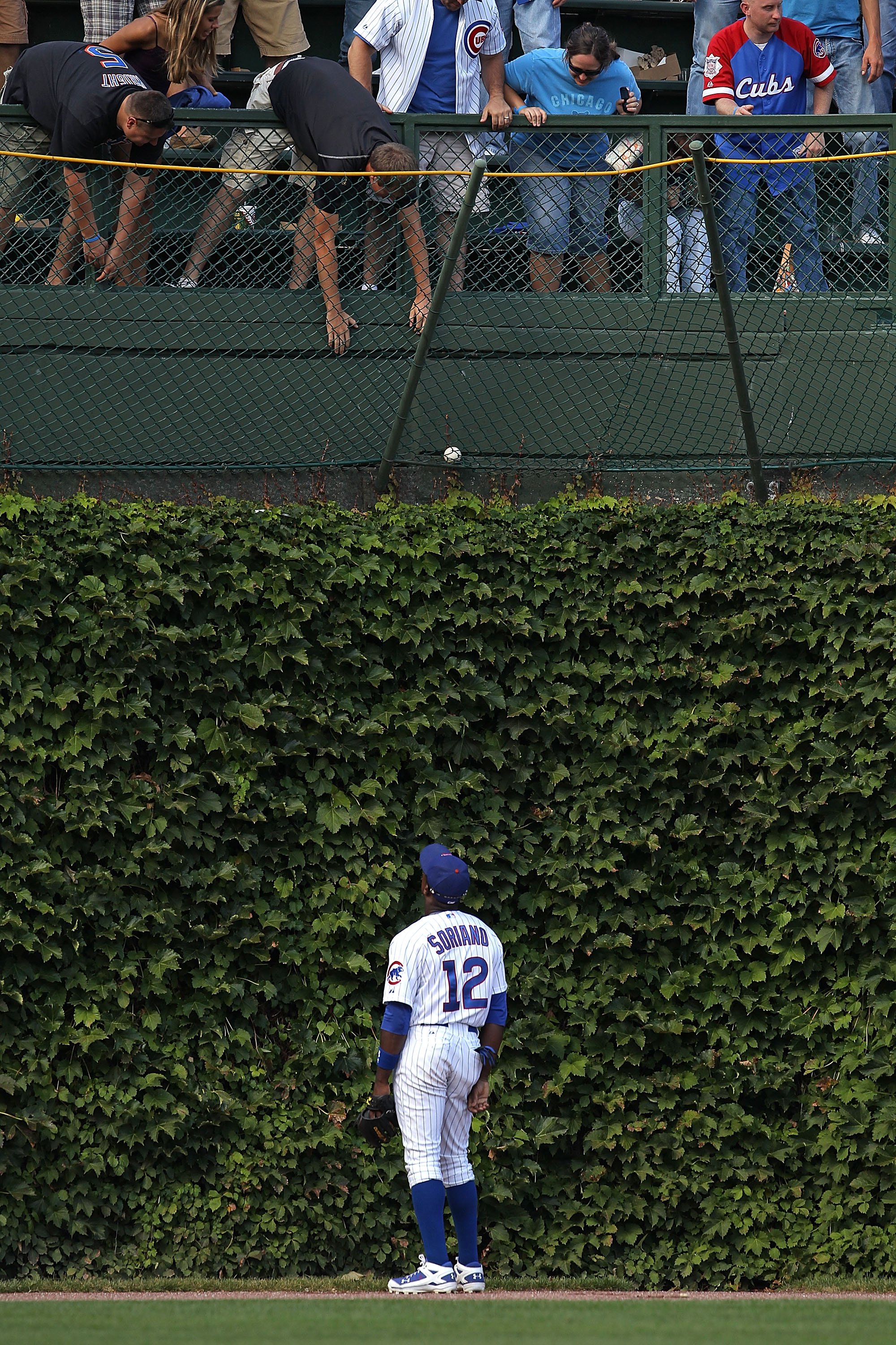 CHICAGO - SEPTEMBER 05: Alfonso Soriano #12 of the Chicago Cubs watches as fans try to grab a home run ball hit by Ike Davis of the New York Mets out of the basket in left field at Wrigley Field on September 5, 2010 in Chicago, Illinois. (Photo by Jonatha