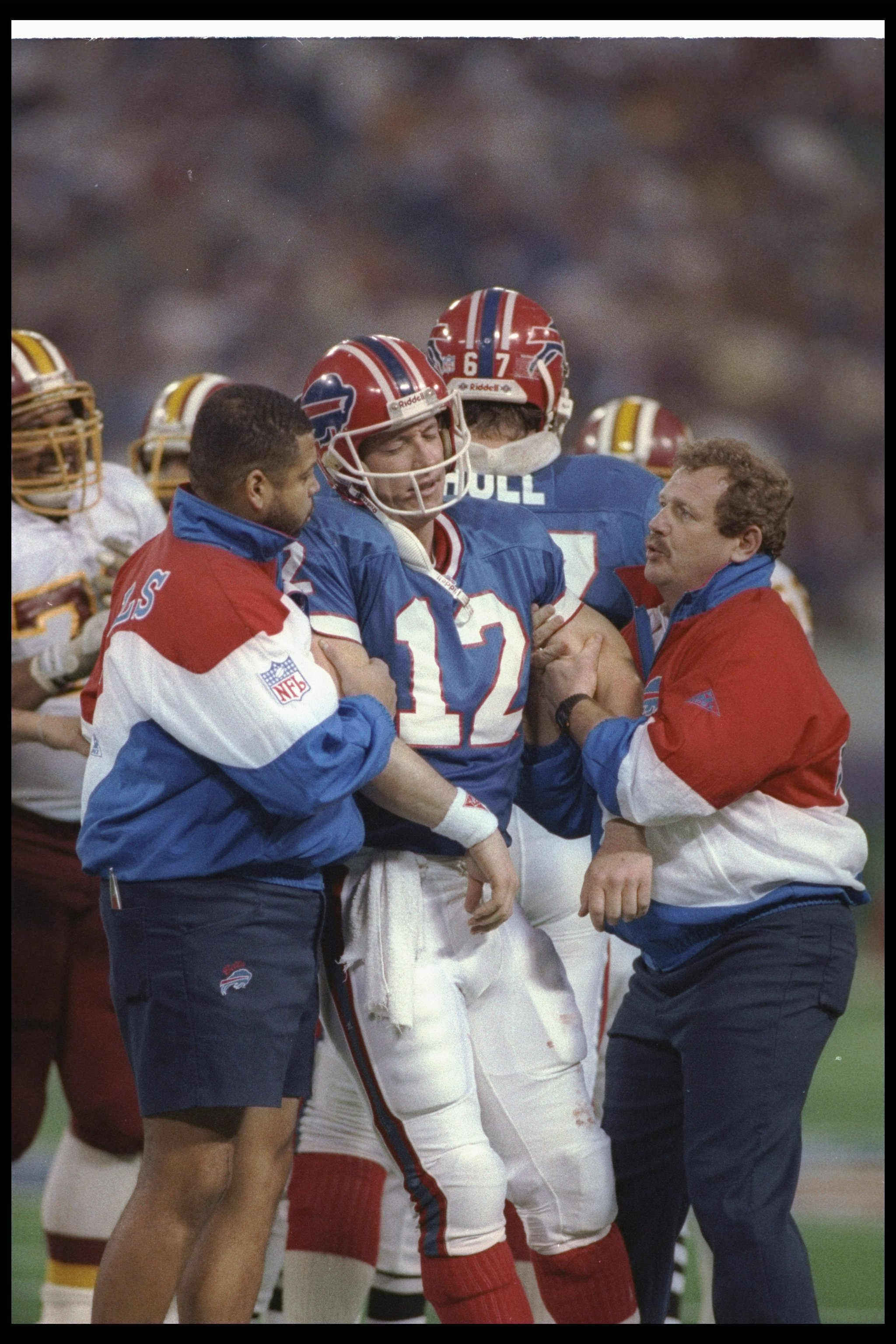 26 Jan 1992:  Quarterback Jim Kelly of the Buffalo Bills is helped off the field during Super Bowl XXVI against the Washington Redskins at the Hubert H. Humphrey Metrodome in Minneapolis, Minnesota.  The Redskins won the game, 37-24. Mandatory Credit: Ric