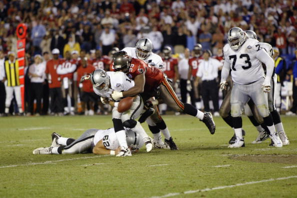 SAN DIEGO - JANUARY 26:  Quarterback Rich Gannon #12 of the Oakland Raiders fumbles the ball after being hit and sacked for a nine yard loss by Warren Sapp #99 of the Tampa Bay Buccaneers on the Oakland 29 yard line at 2:00 of the fourth quarter of Super
