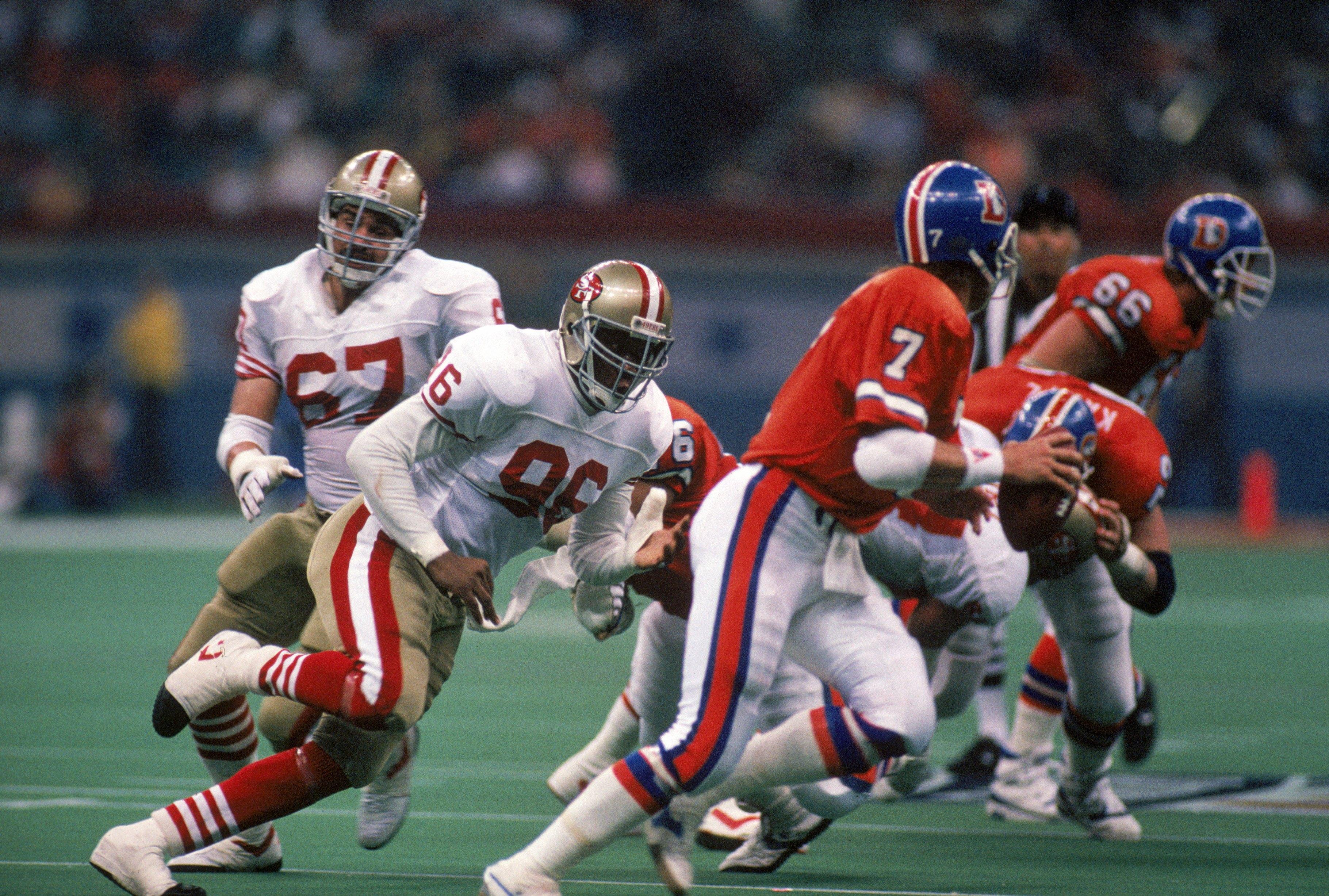 NEW ORLEANS - JANUARY 28:  Defensive end Daniel Stubbs #96 of the San Francisco 49ers pursues Denver Broncos quarterback John Elway #7 in Super Bowl XXIV at Louisiana Superdome on January 28, 1990 in New Orleans, Louisiana.  The 49ers won 55-10.  (Photo b