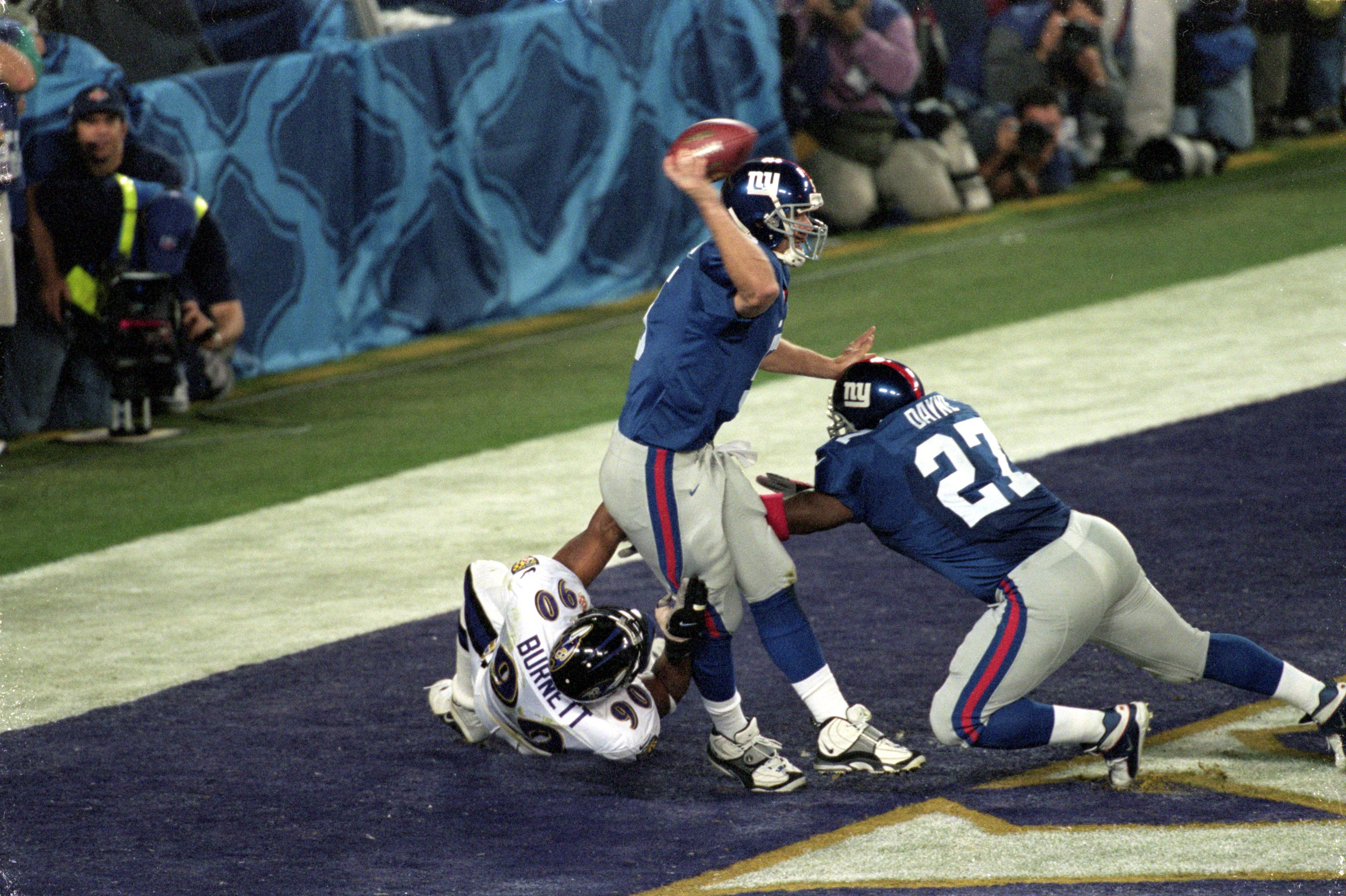 28 Jan 2001:  Quarterback Kerry Collins #5 of the New York Giants gets ready to pass the ball as teammate Ron Dayne #27 tries to hold back Bob Burnett #90 of the Baltimore Ravens during the Super Bowl XXXV Game at the Raymond James Stadium in Tampa, Flori