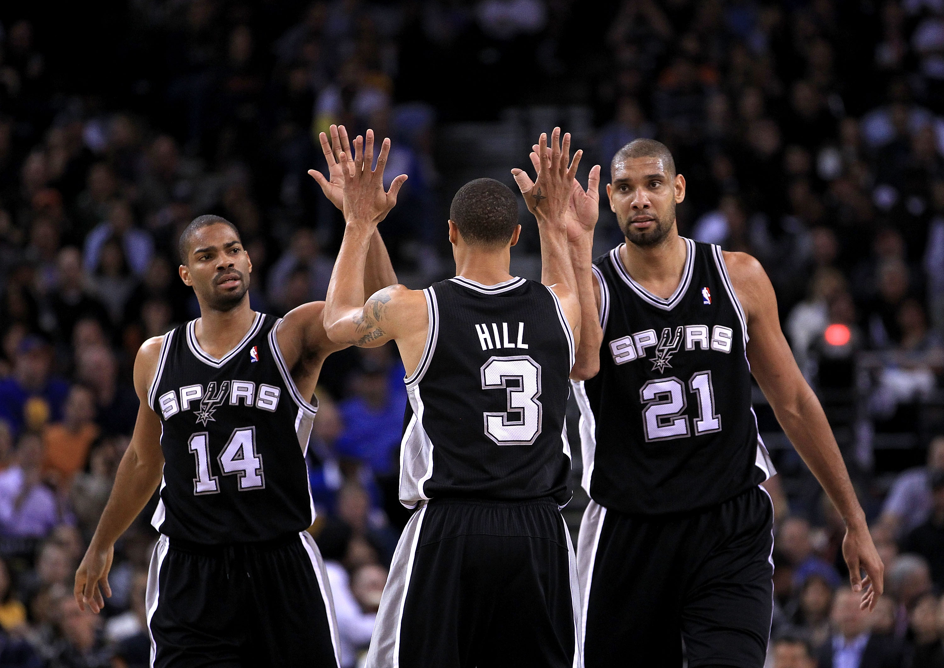 OAKLAND, CA - JANUARY 24:  George Hill #3 of the San Antonio Spurs is congratulated by Tim Duncan #21 and Gary Neal #14 after Hill got fouled during their game against the Golden State Warriors at Oracle Arena on January 24, 2011 in Oakland, California.