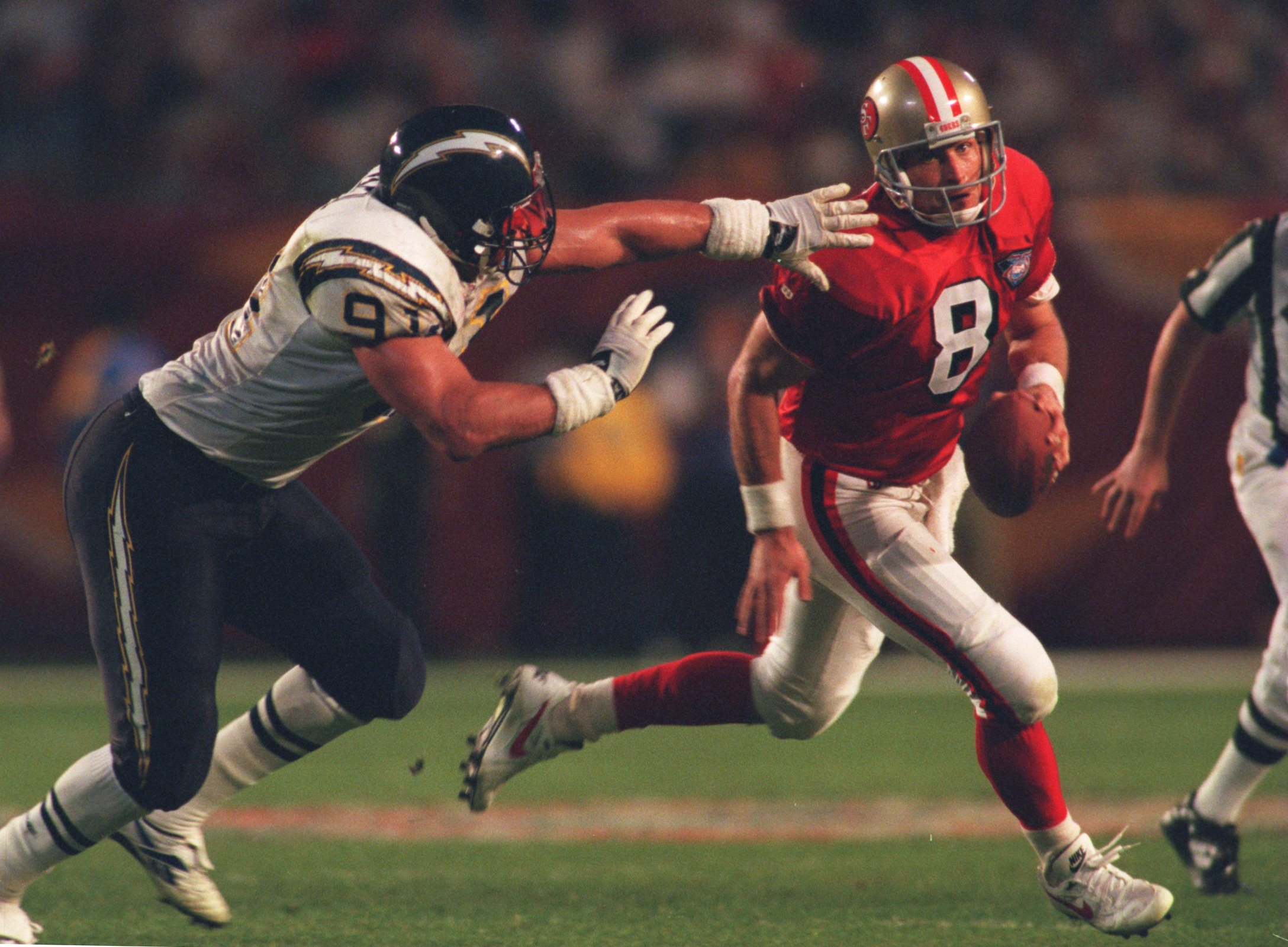 29 Jan 1995: SAN FRANCISCO QUARTERBACK STEVE YOUNG AVOIDS THE OUTSTRETCHED ARMS OF SAN DIEGO DEFENSIVE END LESLIE O'NEAL DURING THE FOURTH QUARTER OF THE SAN FRANCISCO 49ERS VERSUS SAN DIEGO CHARGERS IN SUPER BOWL XXIX AT JOE ROBBIE STADIUM IN MIAMI, FLOR