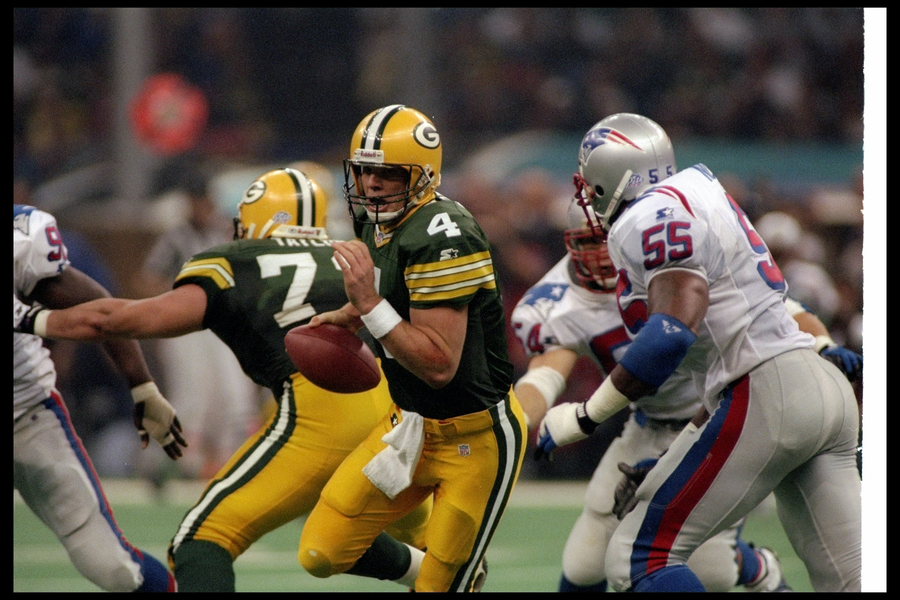26 Jan 1997:  Quarterback Brett Favre of the Green Bay Packers attempts to avoid New England Patriots defensive lineman Willie McGinest during Super Bowl XXXI at the Superdome in New Orleans, Louisiana.  The Packers won the game, 35-21. Mandatory Credit: