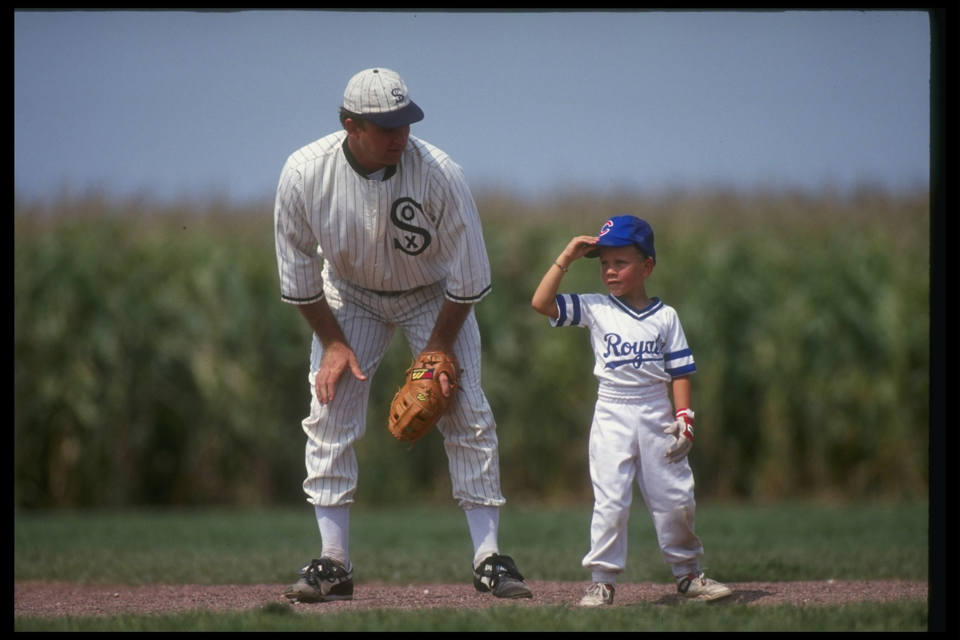 DYERSVILLE, IA - AUGUST 25: A 'ghost player' recreating the role of Chicago White Sox legend Shoeless Joe Jackson plays ball with a young tourist at the baseball field created for the motion picture 'Field of Dreams' on August 25, 1991 in Dyersville, Iowa