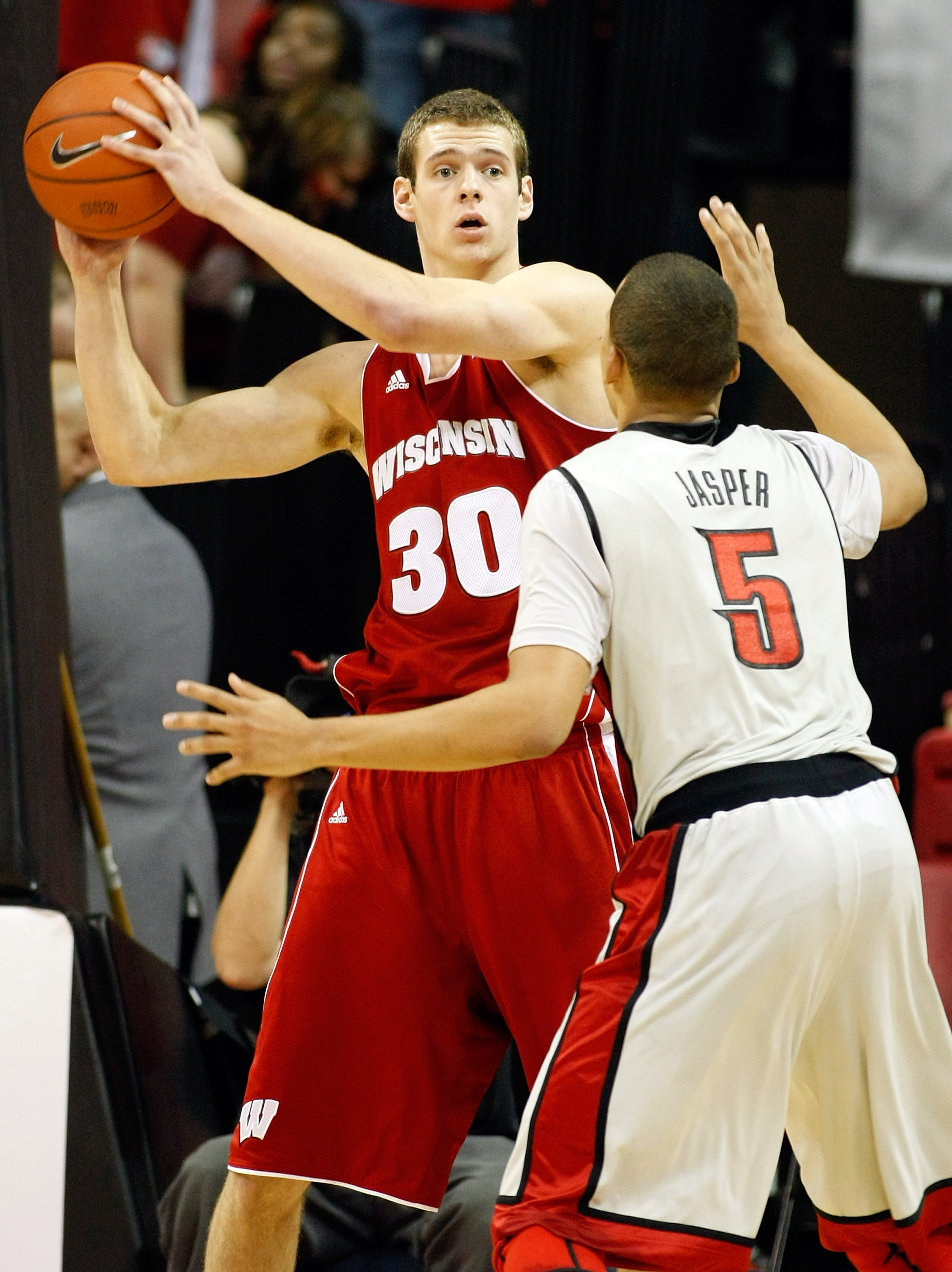 LAS VEGAS - NOVEMBER 20:  Jon Leuer #30 of the Wisconsin Badgers looks to pass the ball inbounds as Derrick Jasper #5 of the UNLV Rebels defends during their game at the Thomas & Mack Center November 20, 2010 in Las Vegas, Nevada. UNLV won 68-65.  (Photo