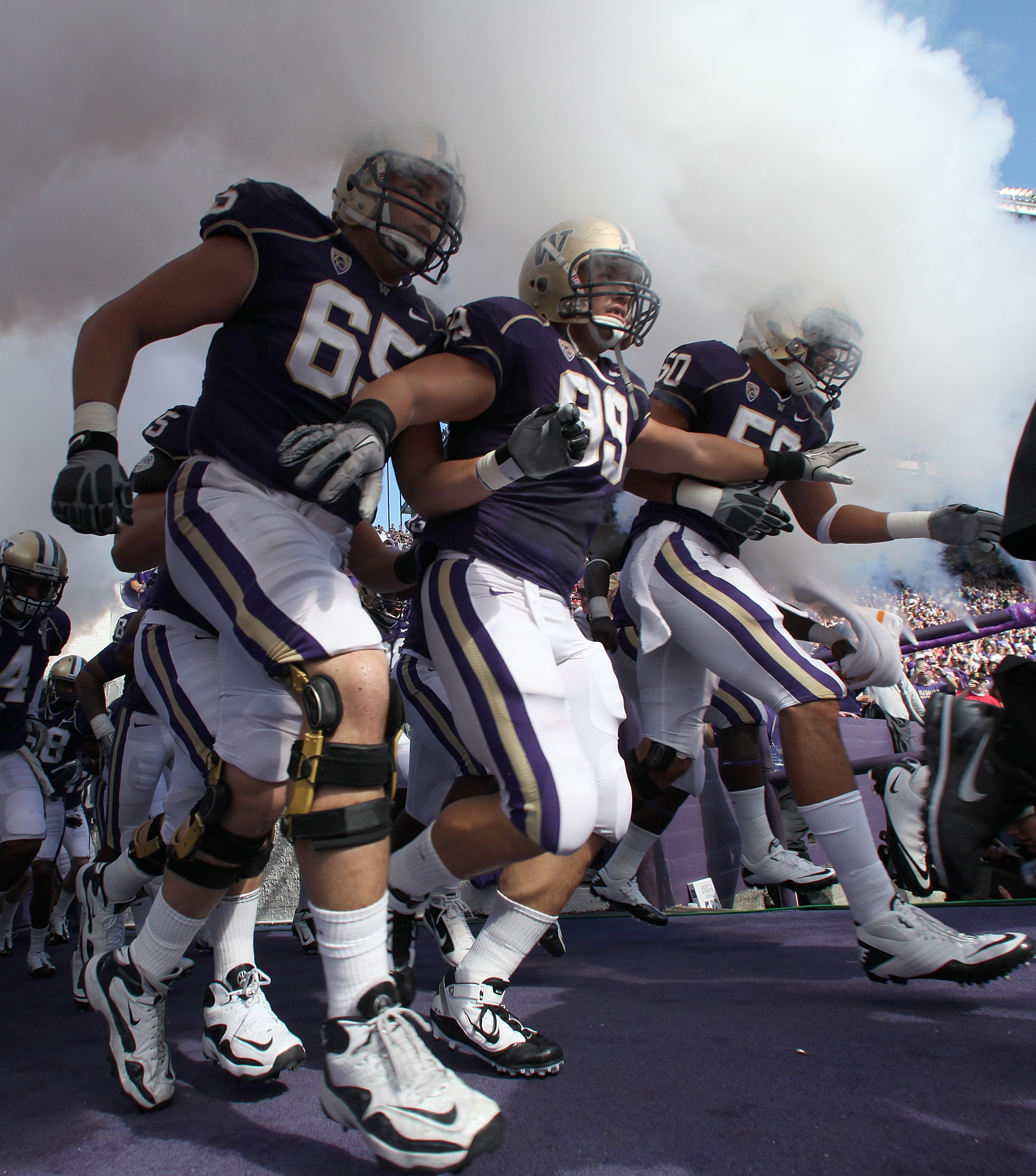 SEATTLE - SEPTEMBER 18:  Ryan Tolar #65, Cameron Elisara #99, and Kalani Aldrich #50 of the Washington Huskies run out of the tunnel prior to the game against the Nebraska Cornhuskers on September 18, 2010 at Husky Stadium in Seattle, Washington. The Corn