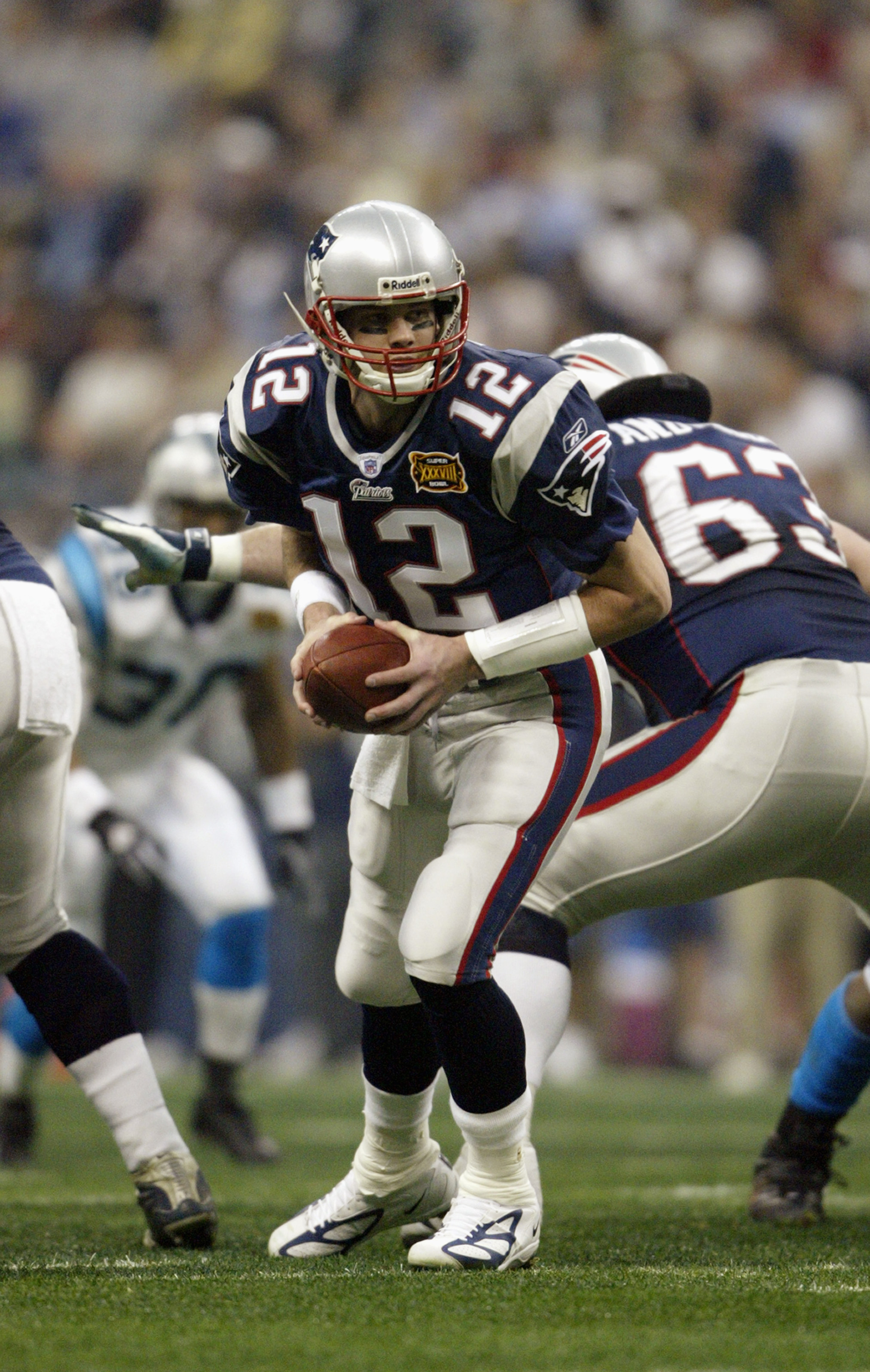 HOUSTON - FEBRUARY 1:  Qaurterback Tom Brady #12 of the New England Patriots attempts a hand off against the Carolina Panthers during Super Bowl XXXVIII at Reliant Stadium on February 1, 2004 in Houston, Texas.  The Patriots defeated the Panthers 32-29.